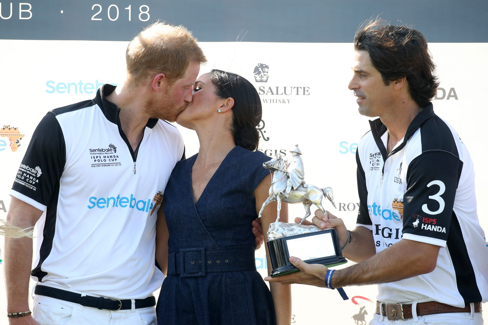 Prince Harry and Meghan Markle kissing at the Sentebale Polo 2018 charity event