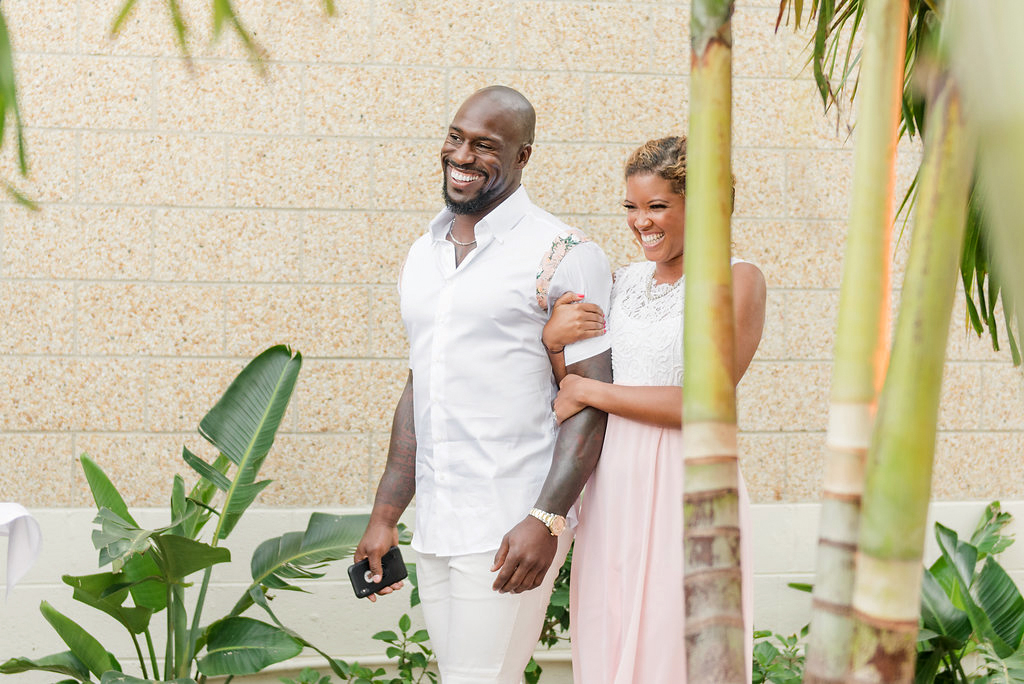 couple arriving walking by tropical plants