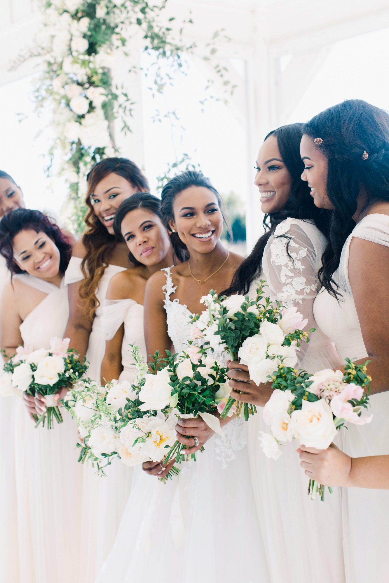 wedding bridesmaids in white holding white flowers