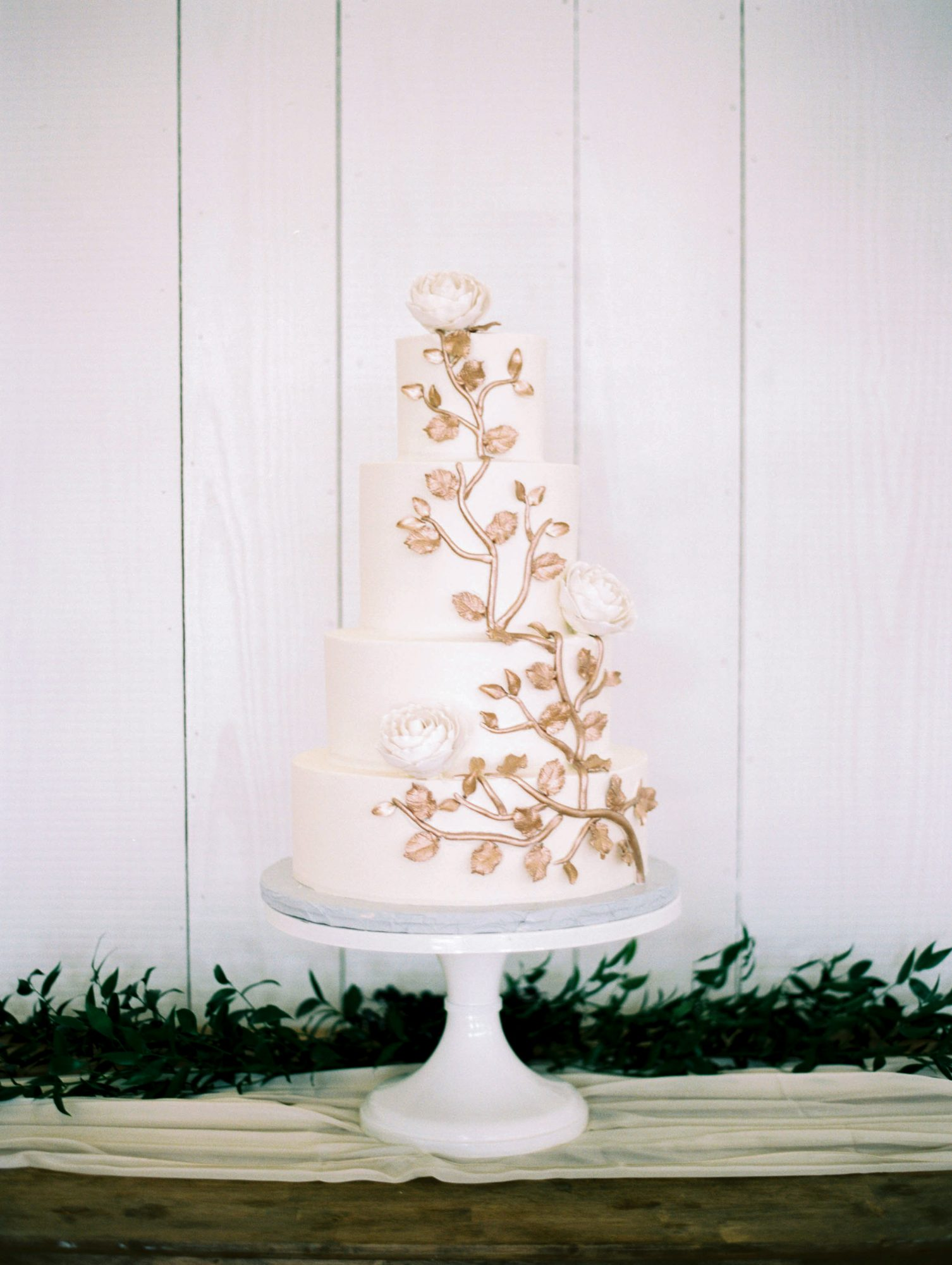 white wedding cake with white flowers and gold leaves