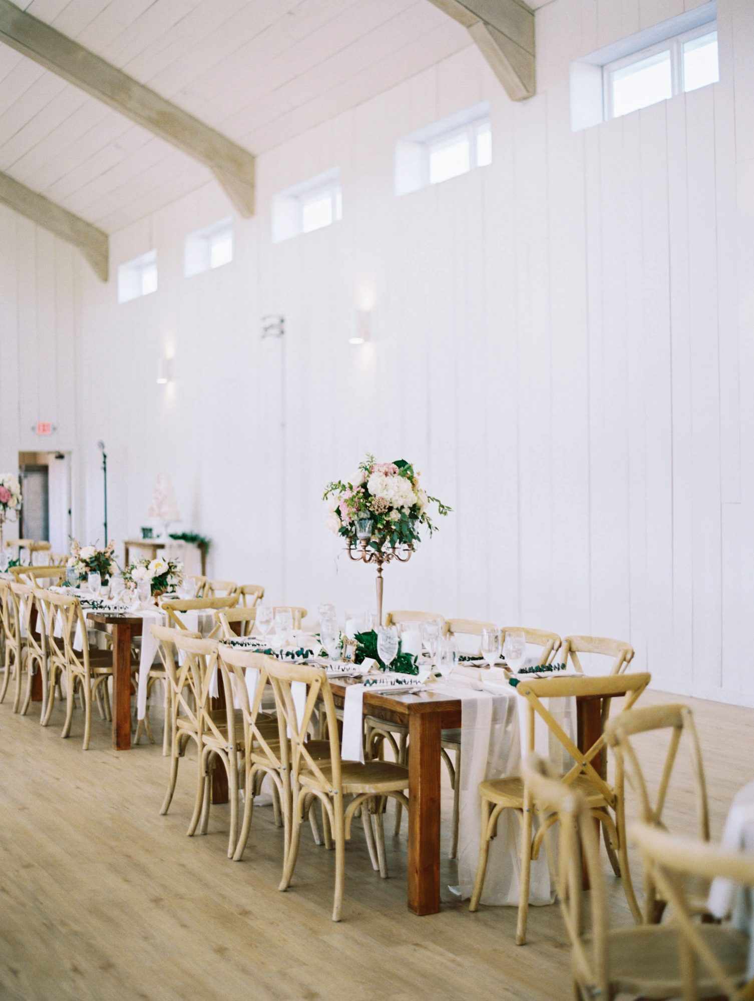 wedding reception tables with tall floral centerpiece