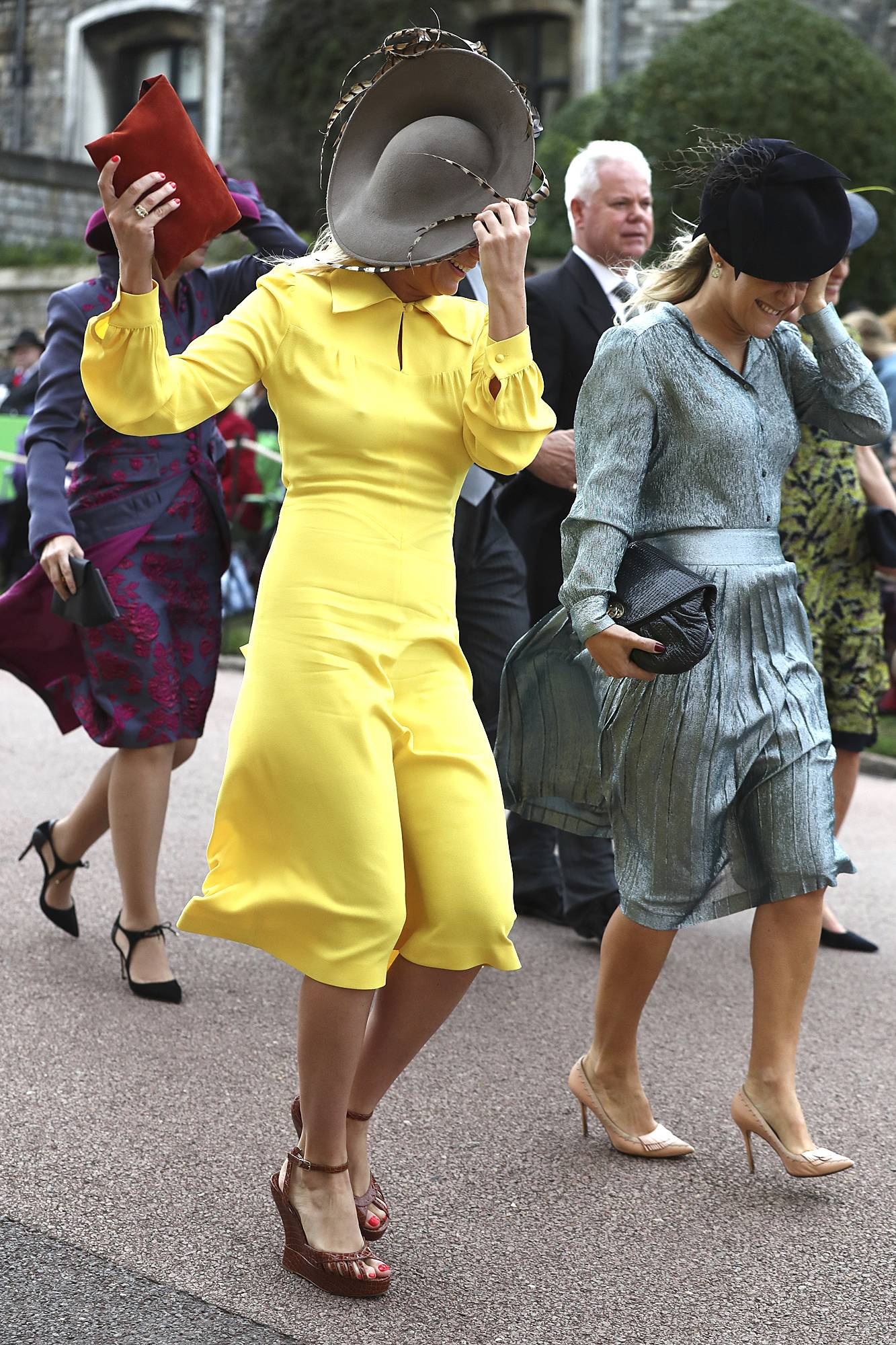 guests fight the wind as they arrive at princess eugenie's royal wedding