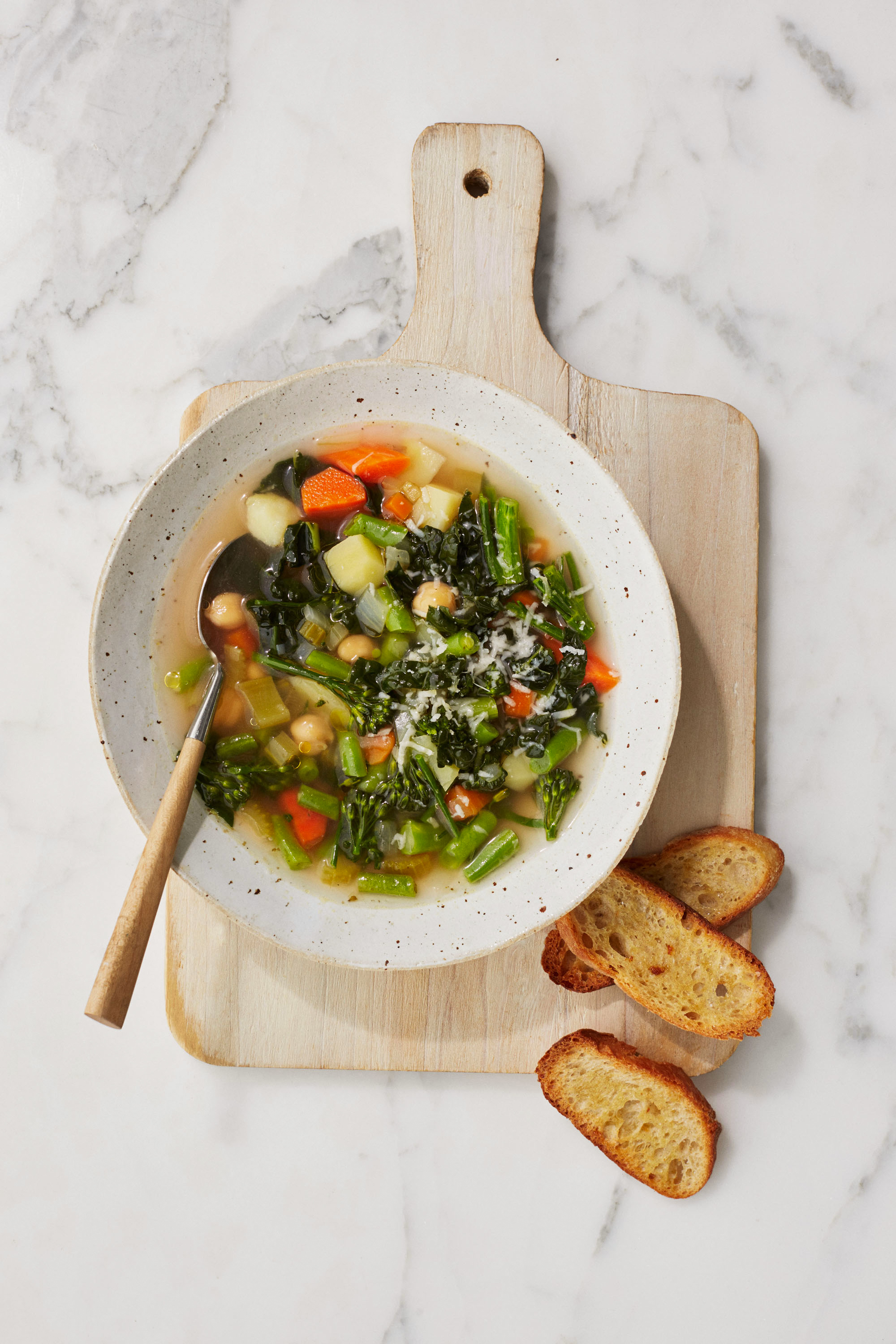 homemade vegetable soup with toasted bread on cutting board