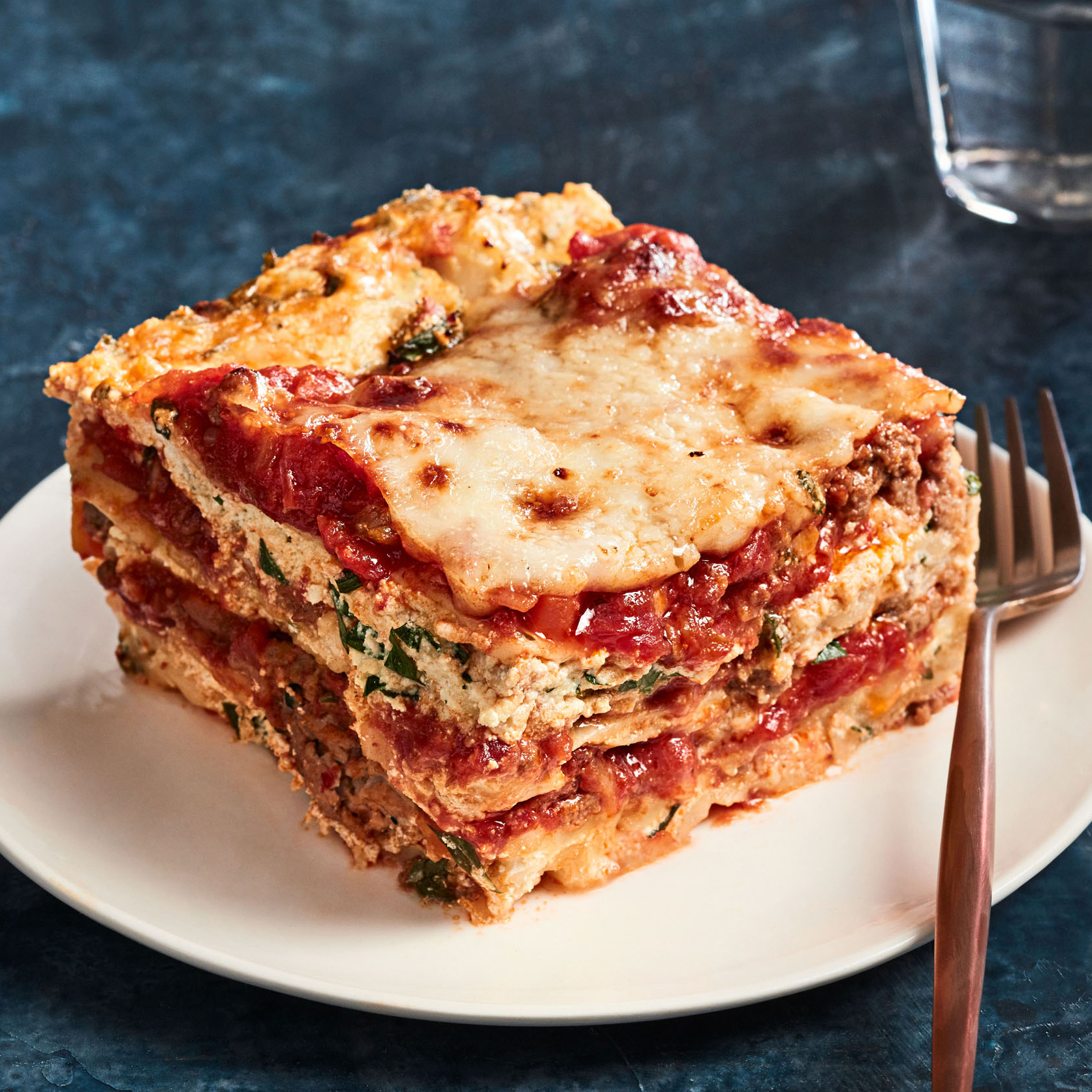 ultimate lasagna slice on plate with fork
