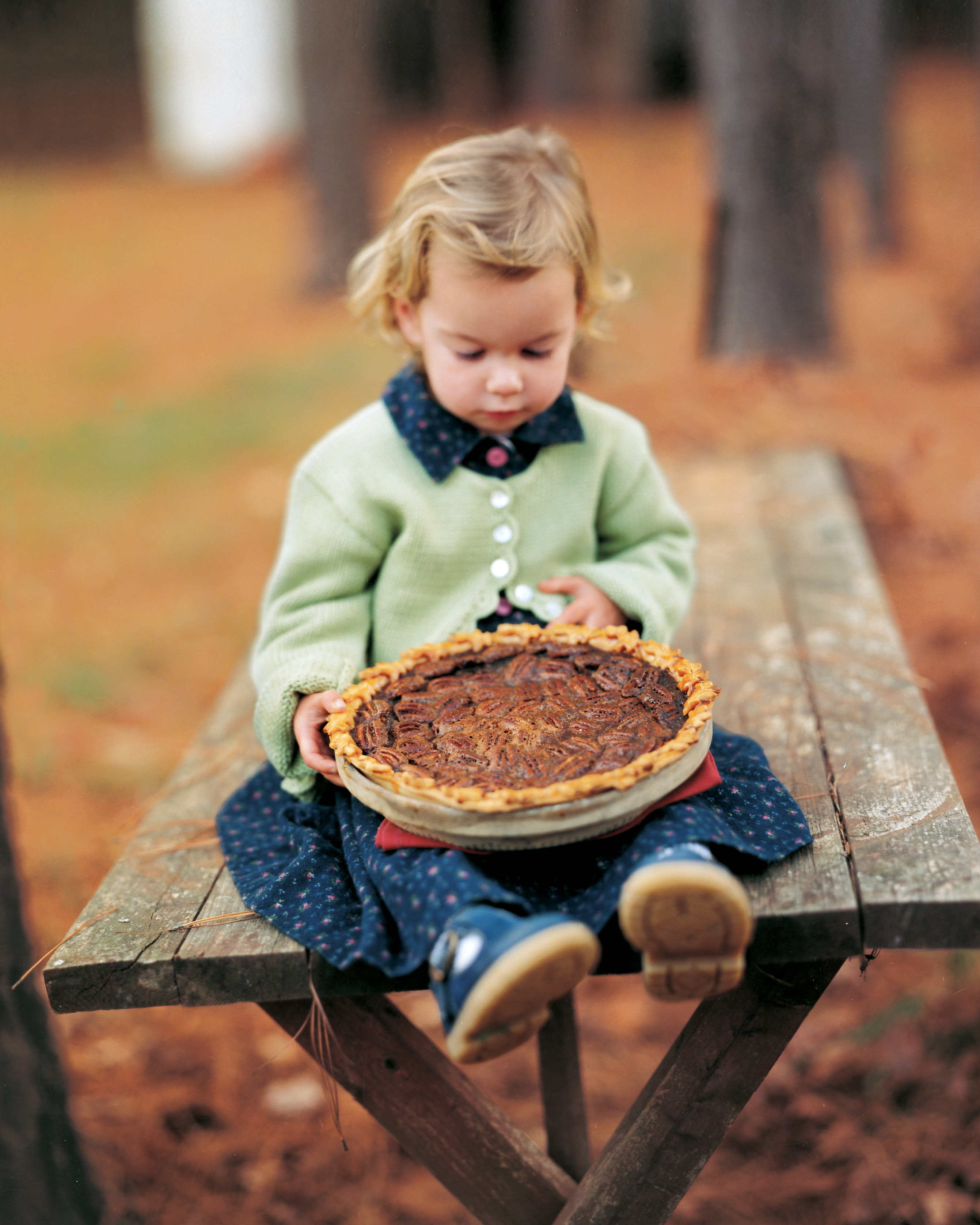 girl on picnic table holding pecan pie