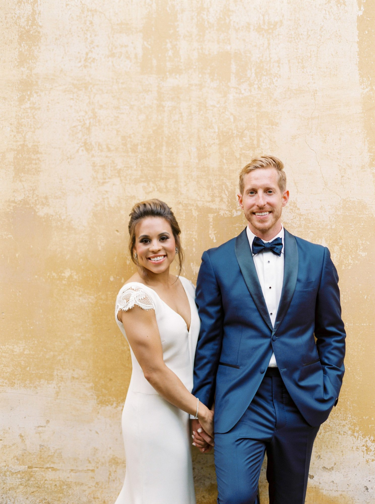 wedding couple posing in front of stone wall