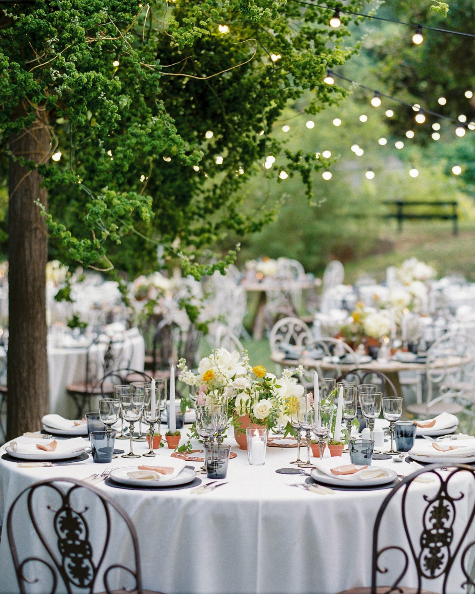 outdoor reception tables with colorful floral arrangements and candles