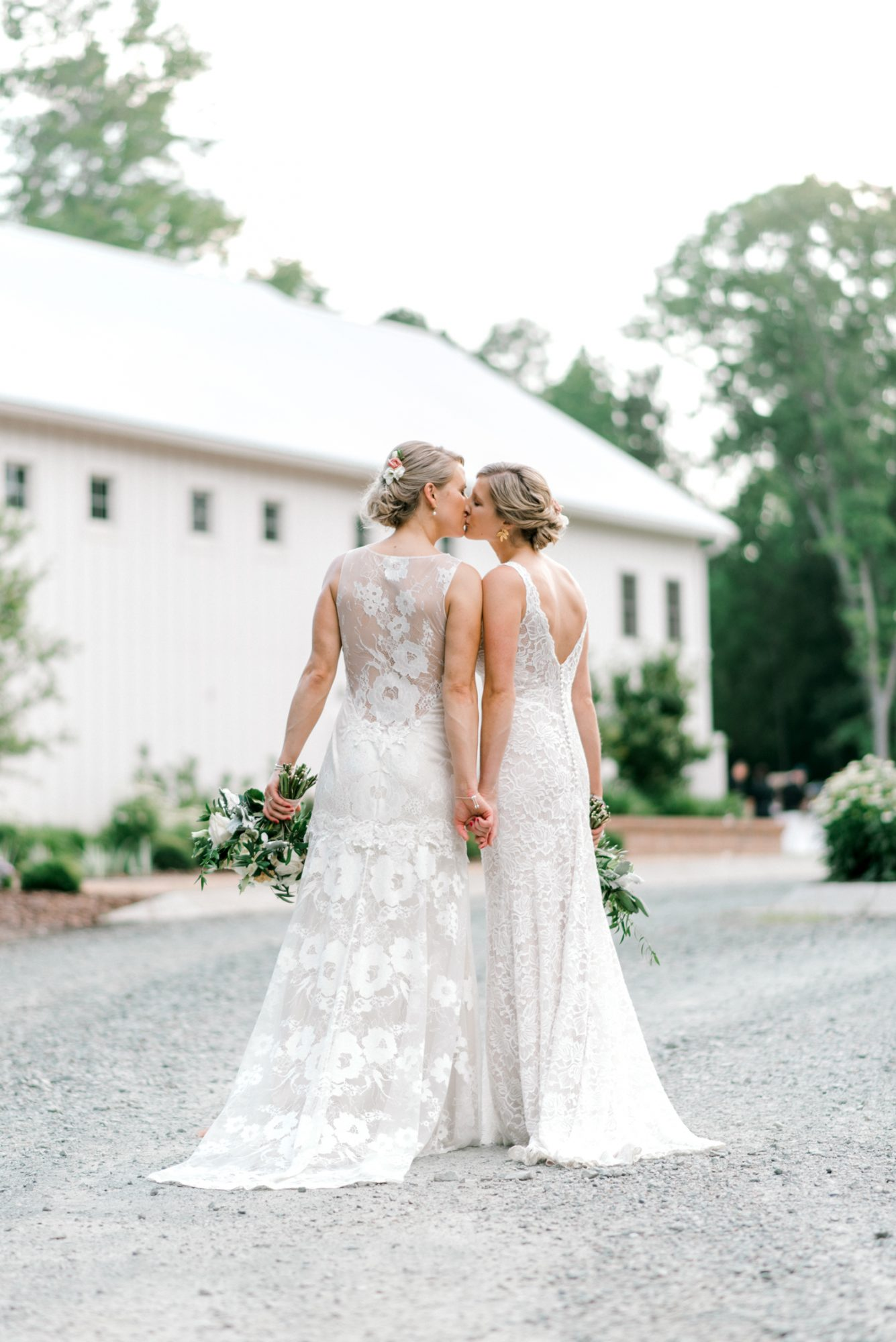 paige and kristine wedding brides kissing by barn