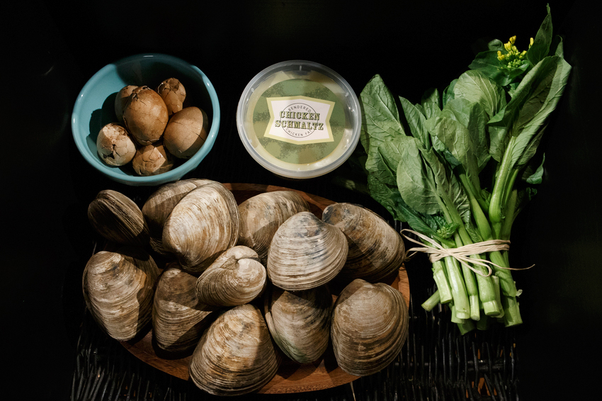 chinese tea eggs clams and greens against black background