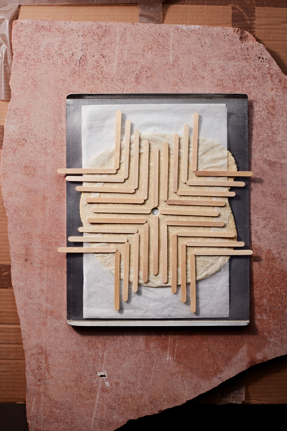 popsicle sticks creating a pattern on pie crust