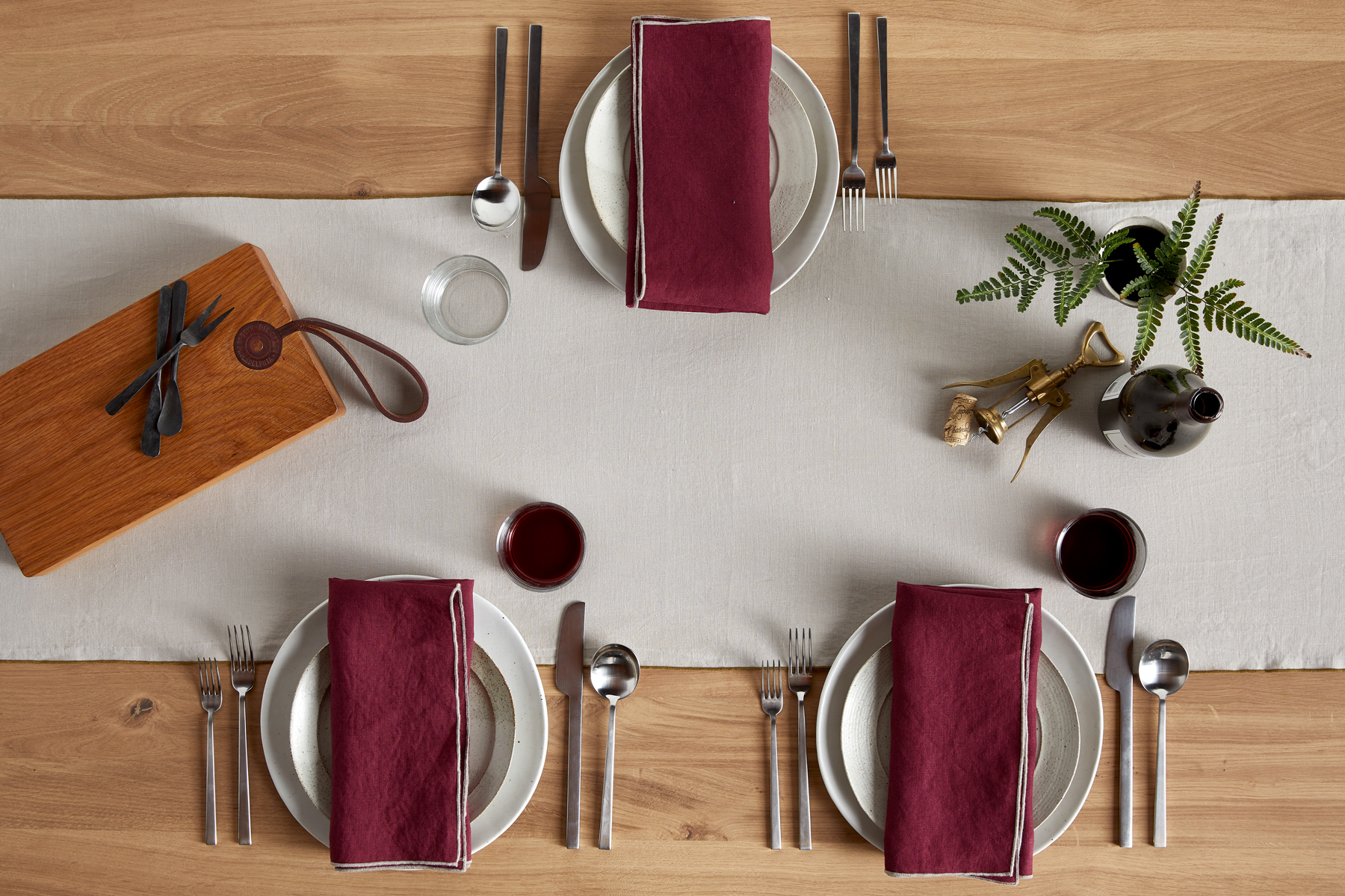 table setting with beige table runner and burgundy napkins