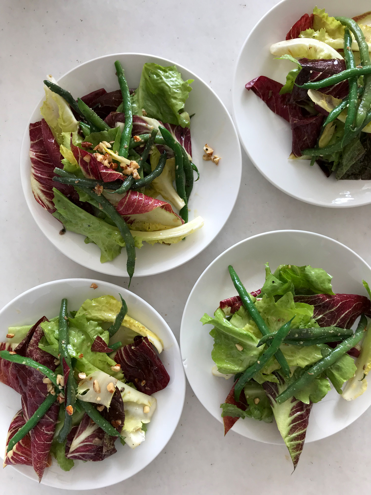 four plated green bean salads in white bowls