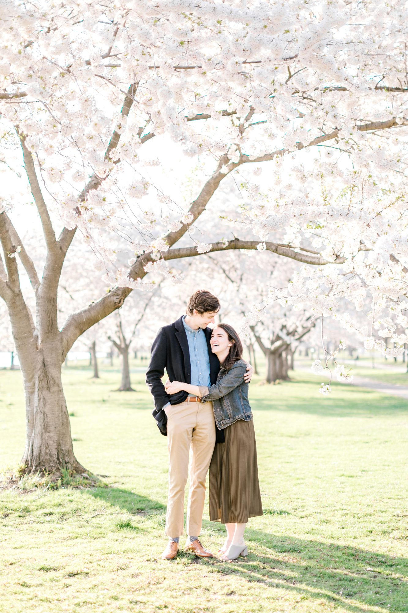 couple hugging under tree engagement
