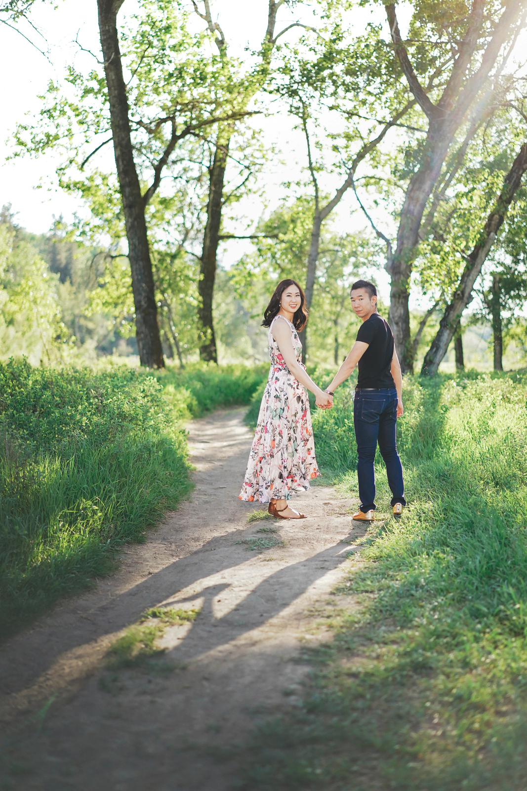 couple walking on greenery path engagement