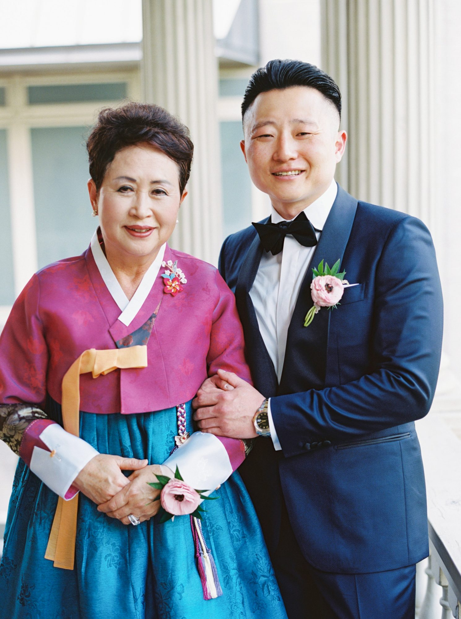groom posing with mother in wedding attire