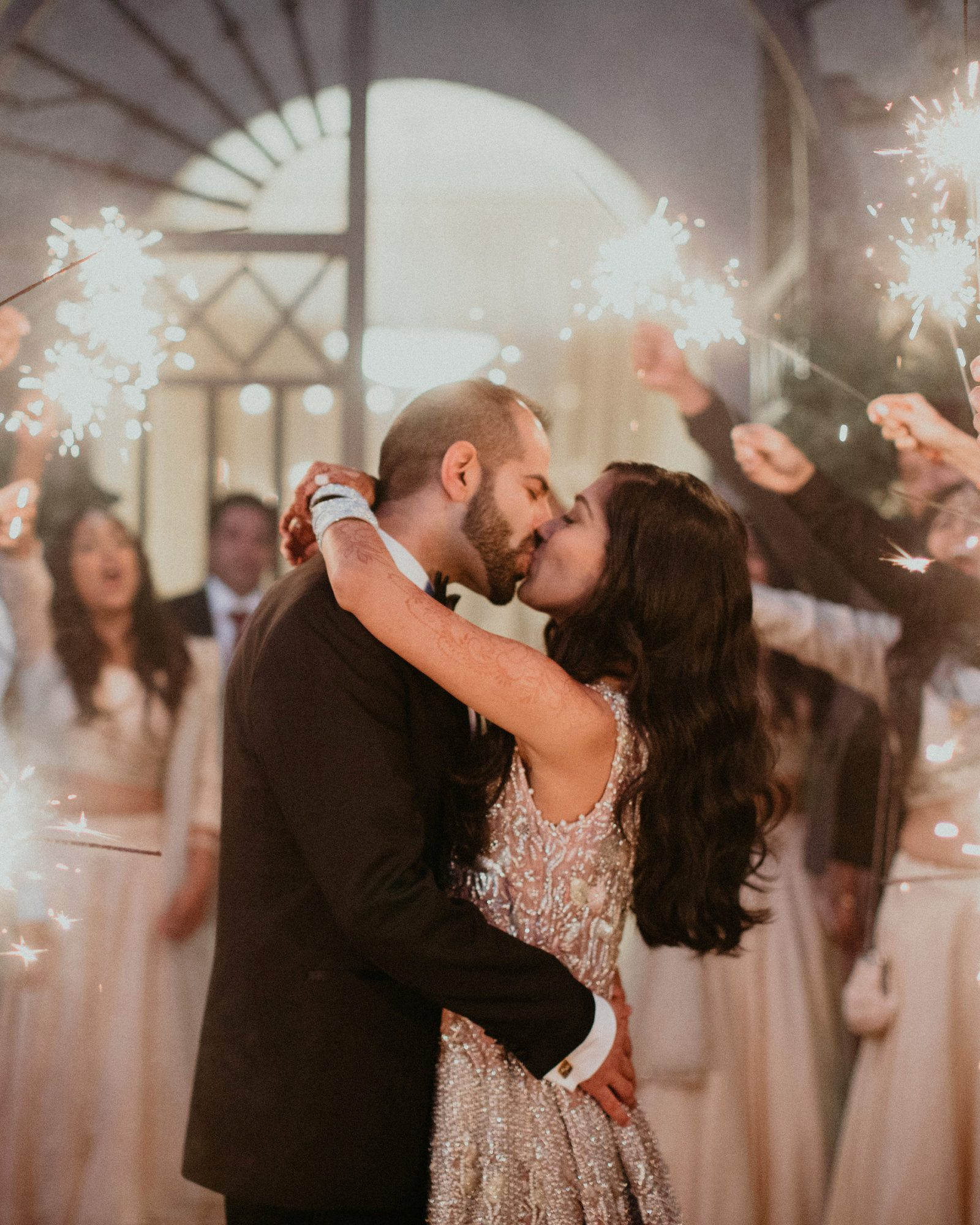 wedding couple kissing with sparkler send off