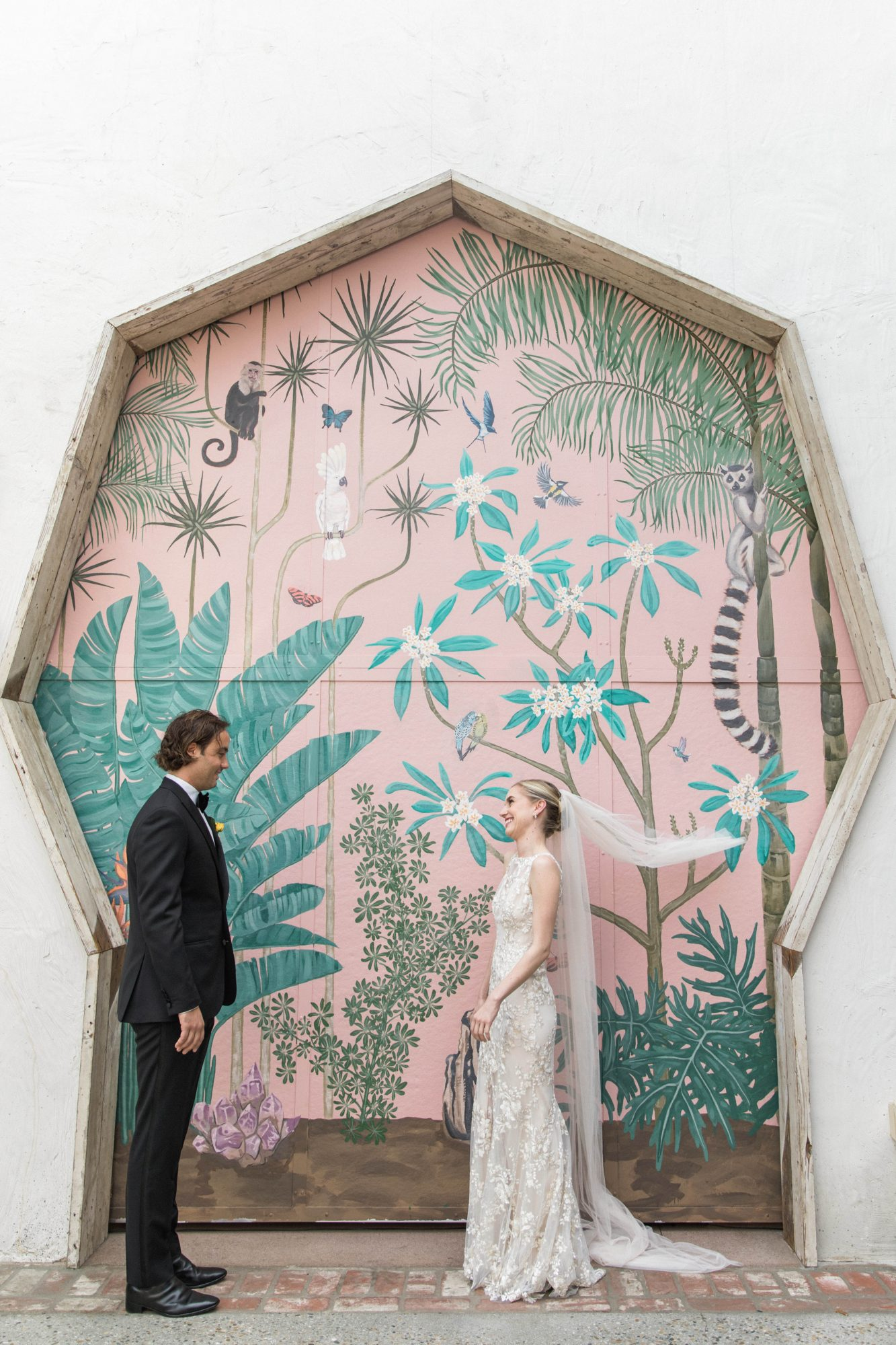 bride and groom first look in front of painted wall
