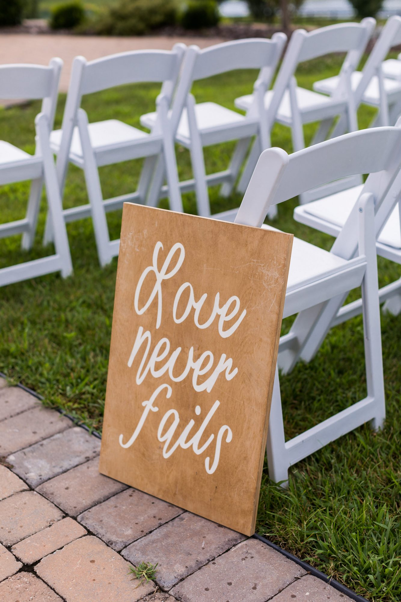 cara chamique wedding love quote on sign by ceremony chair