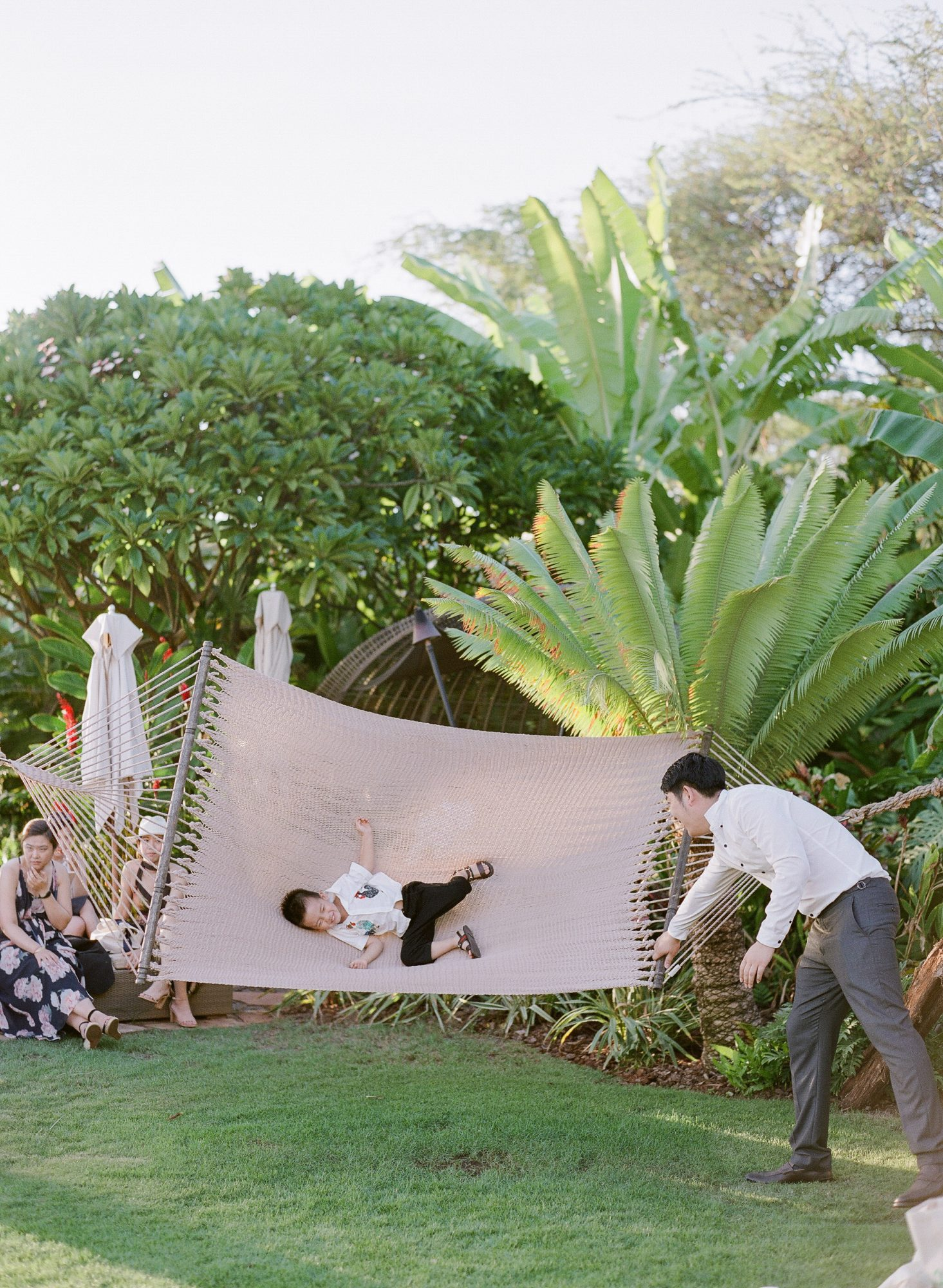 hawaiian wedding guests enjoy swing hammock