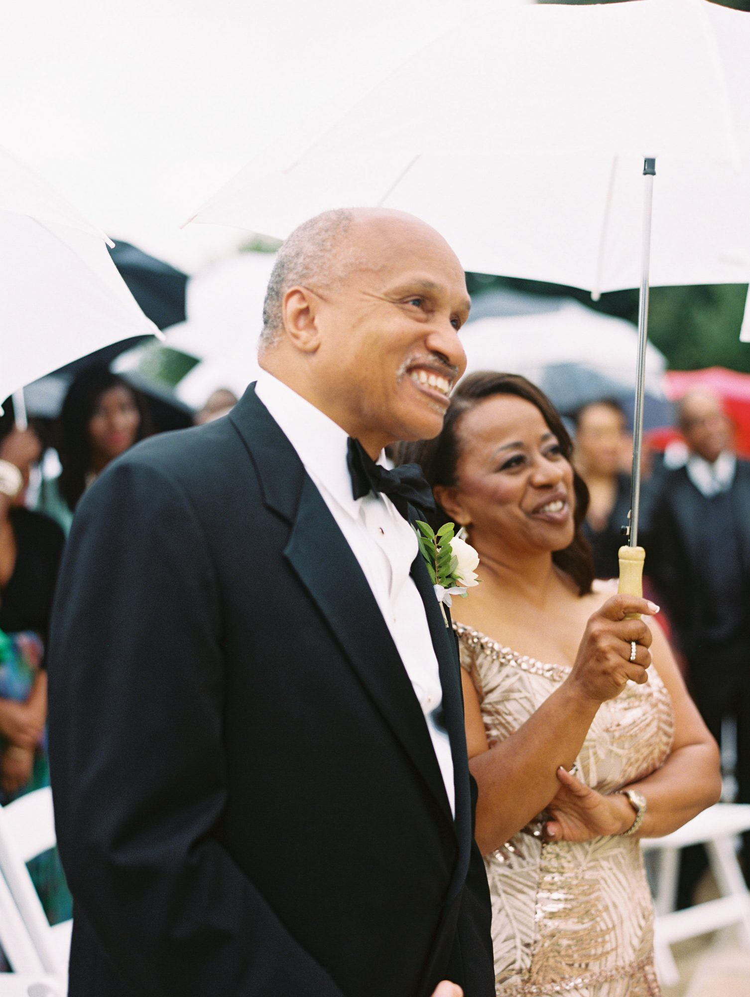 melissa justen wedding ceremony parents with umbrella