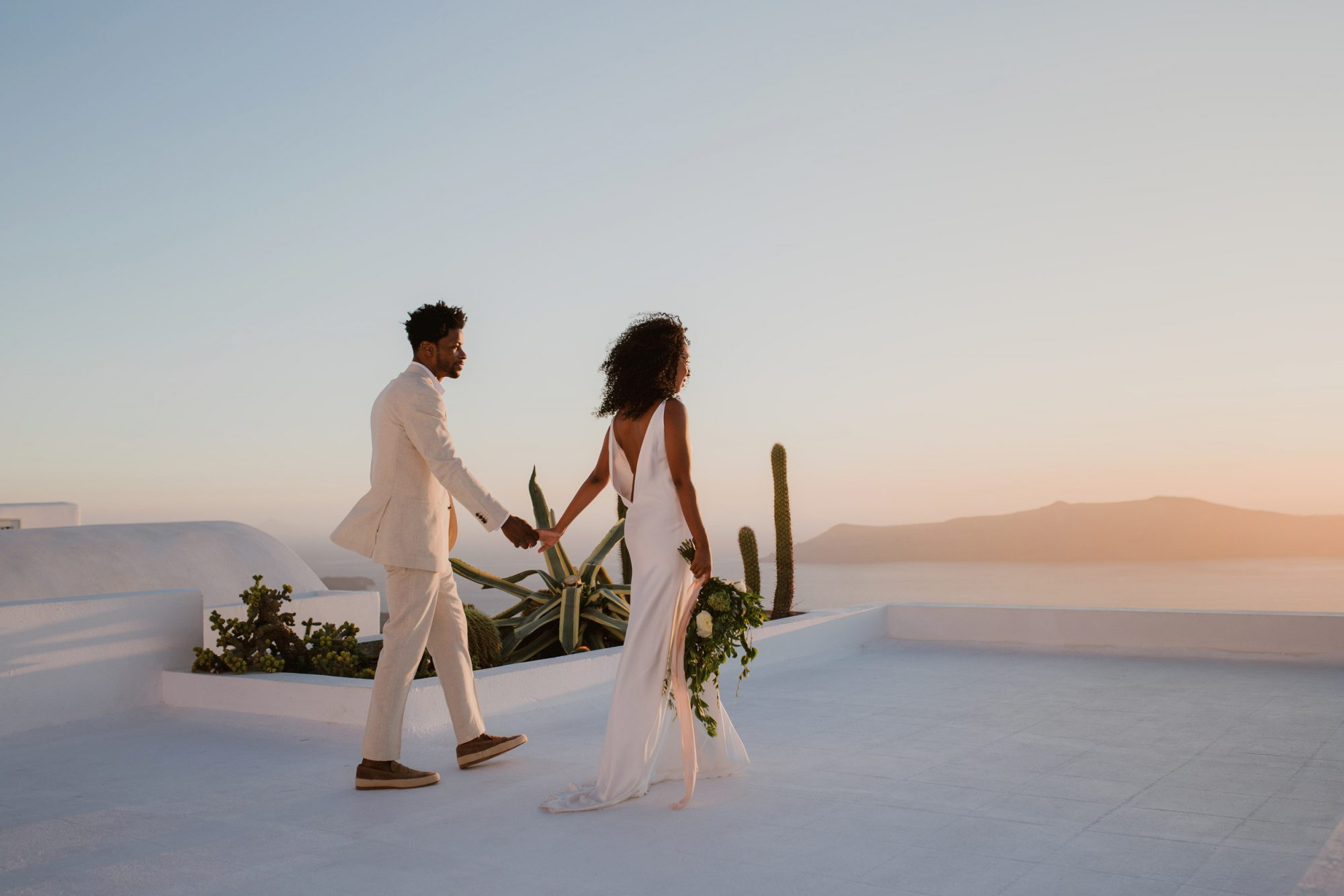 elopement outfit inspiration couple holding hands viewing sunset