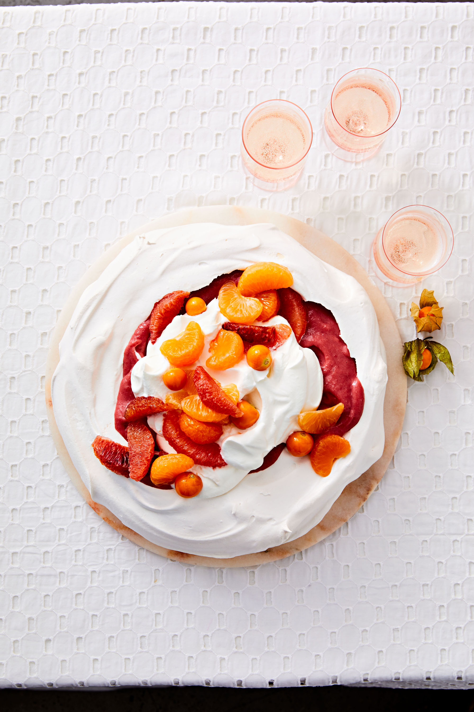 cranberry curd and citrus pavlova with sliced oranges