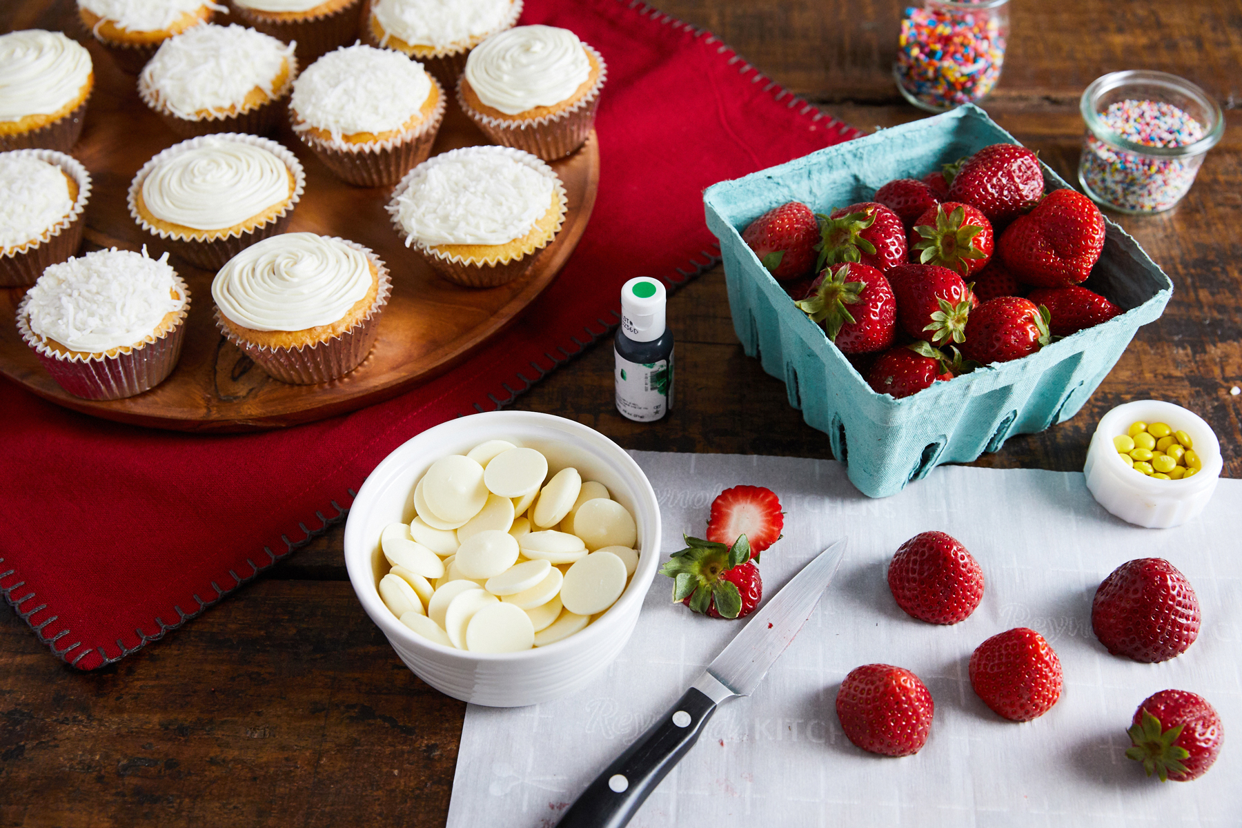 cut strawberries with vanilla cupcakes in background