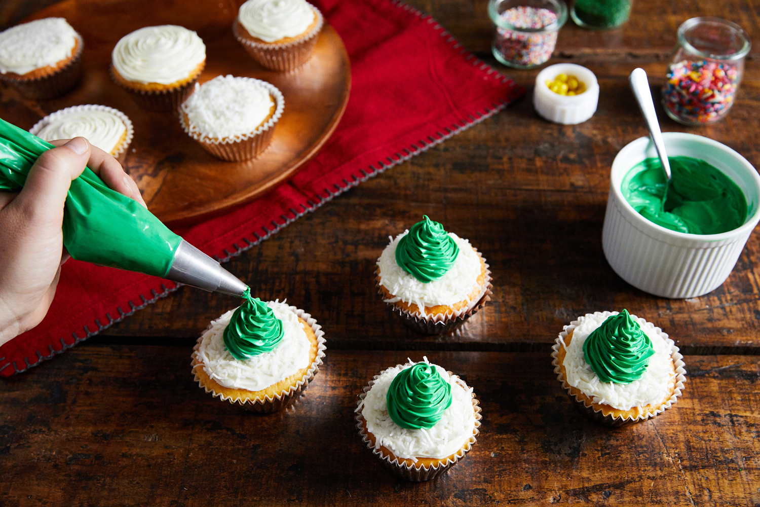 piping green frosted trees atop vanilla cupcakes