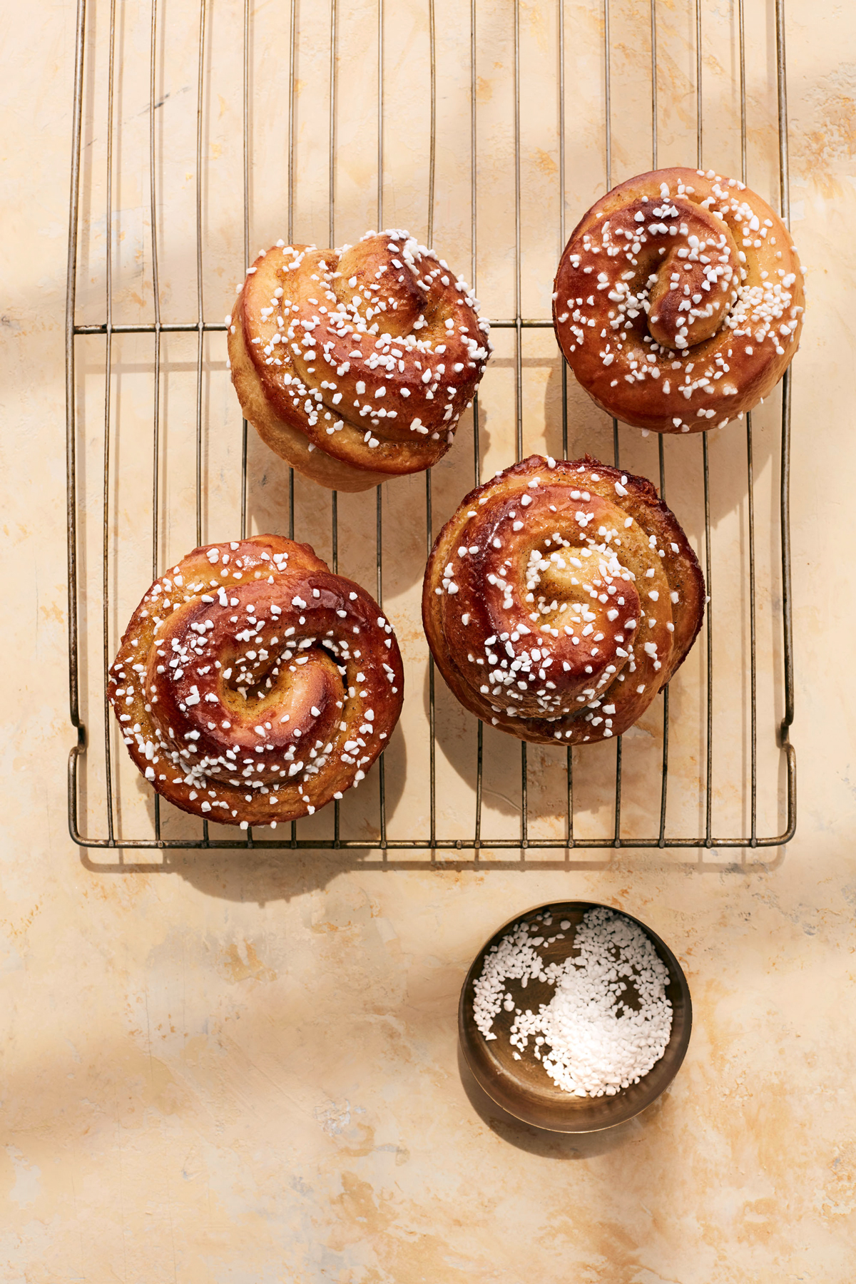 orange cardamom morning buns on cooling rack topped with sanding sugar