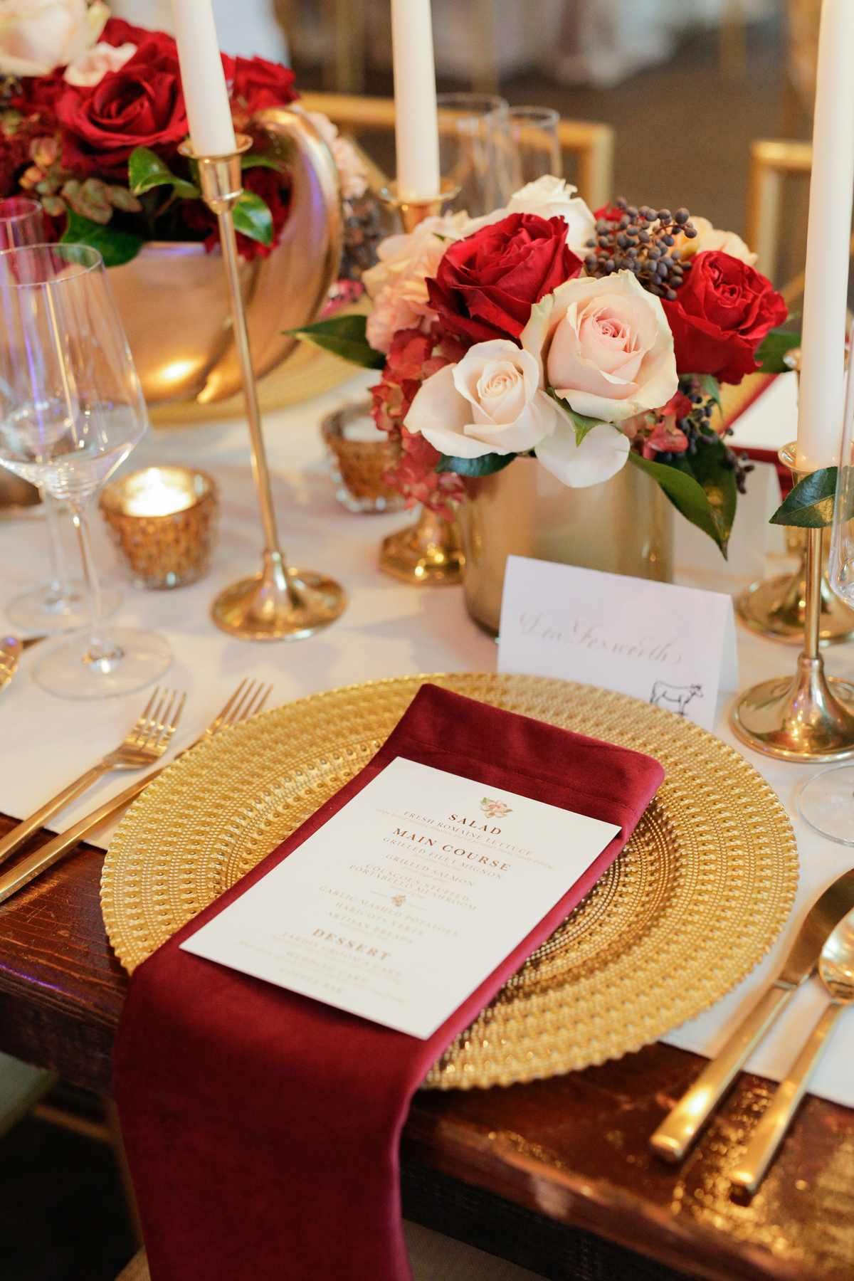 elizabeth seth wedding place setting with gold plates and red napkins