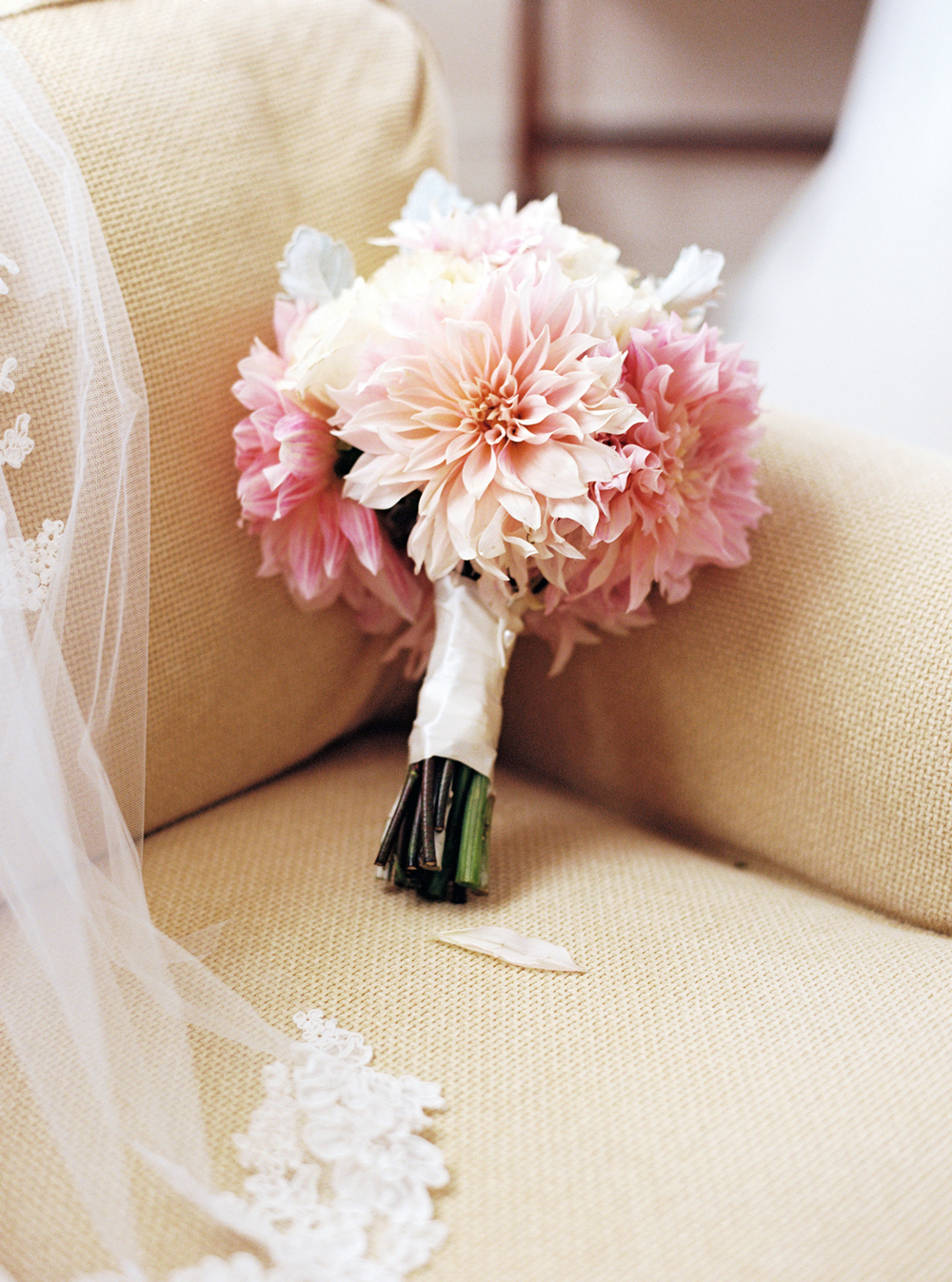 single flower wedding bouquet pink dahlias on tan couch
