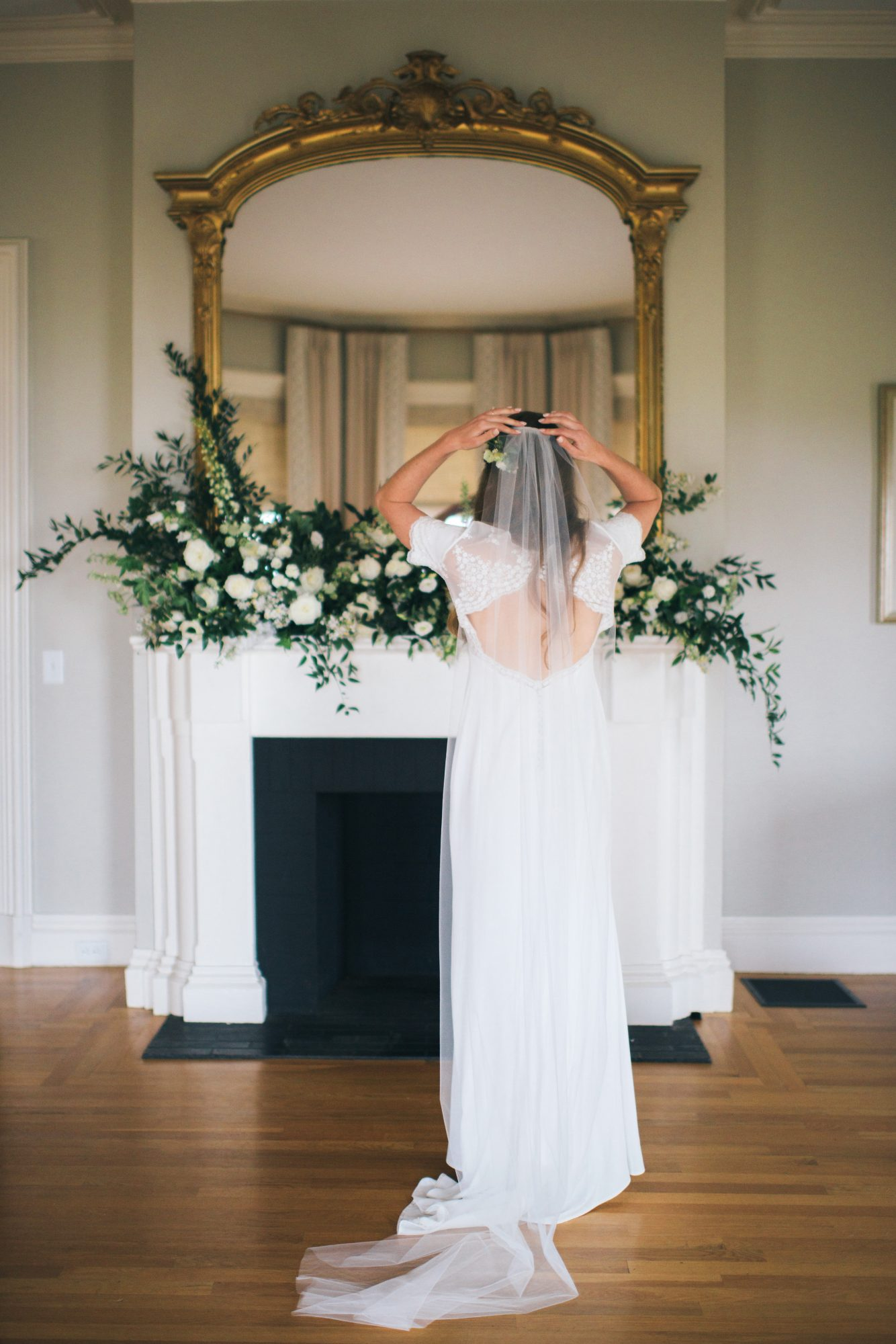 bride in dress looking in mirror above fire place white flowers