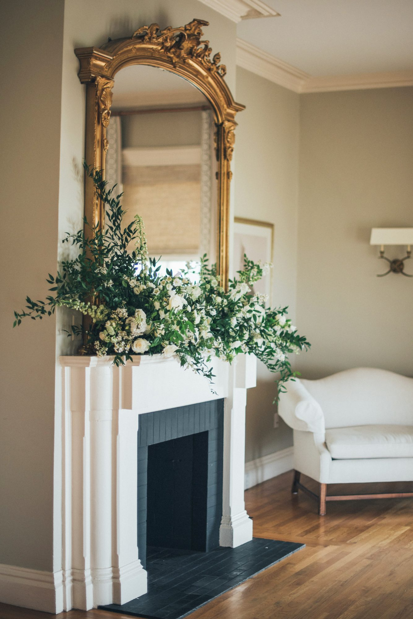 fireplace with white flowers large mirror above