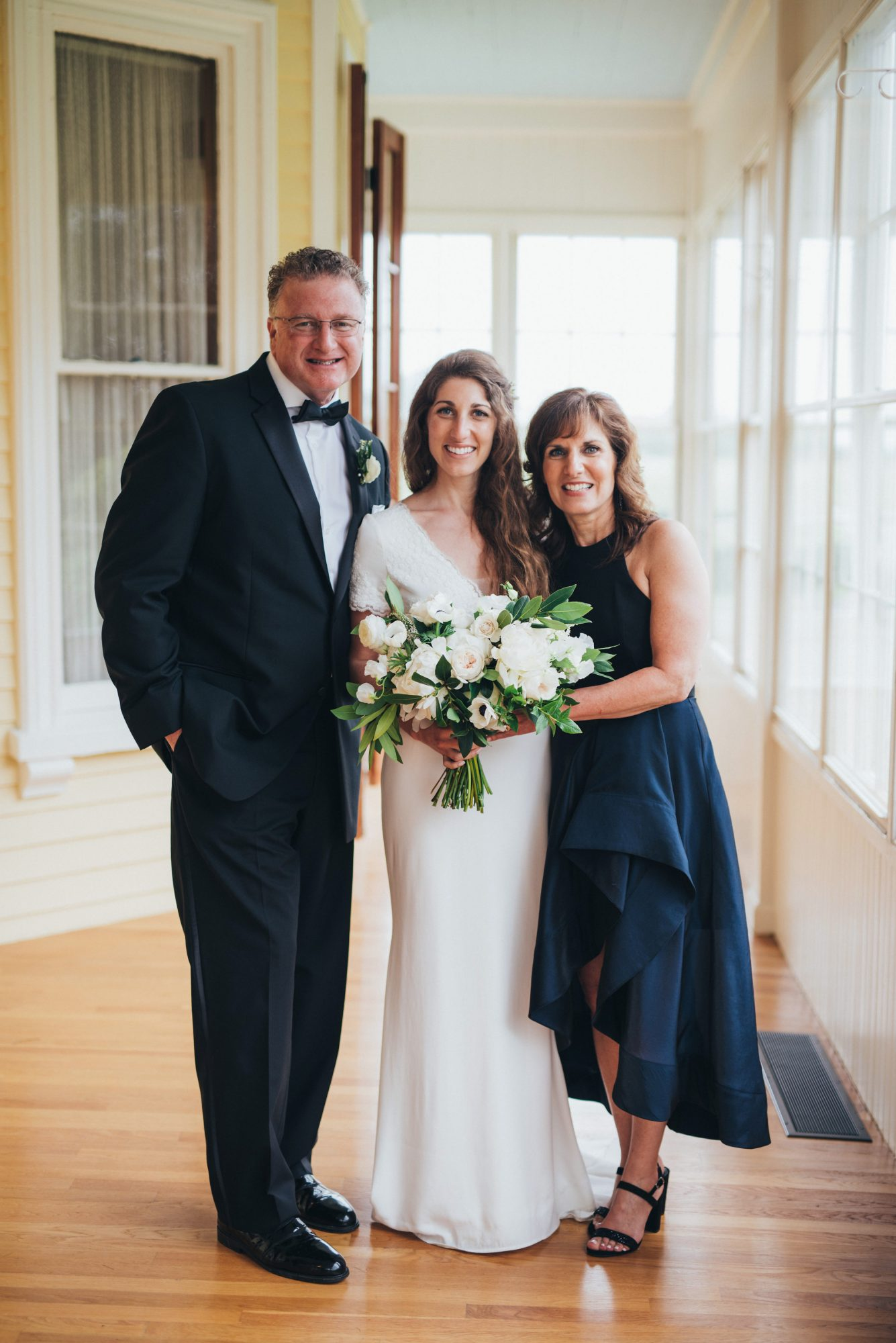 bride poses with parents on porch