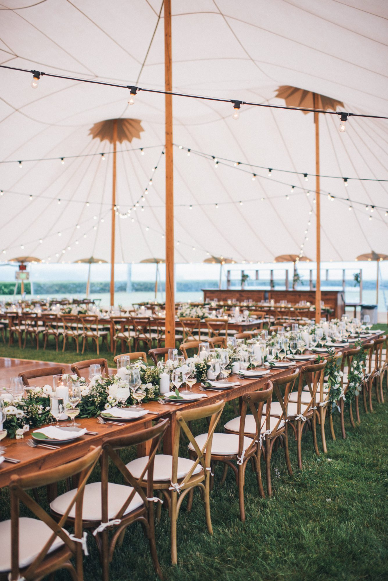 reception tables and chair lineup under tent with lighting