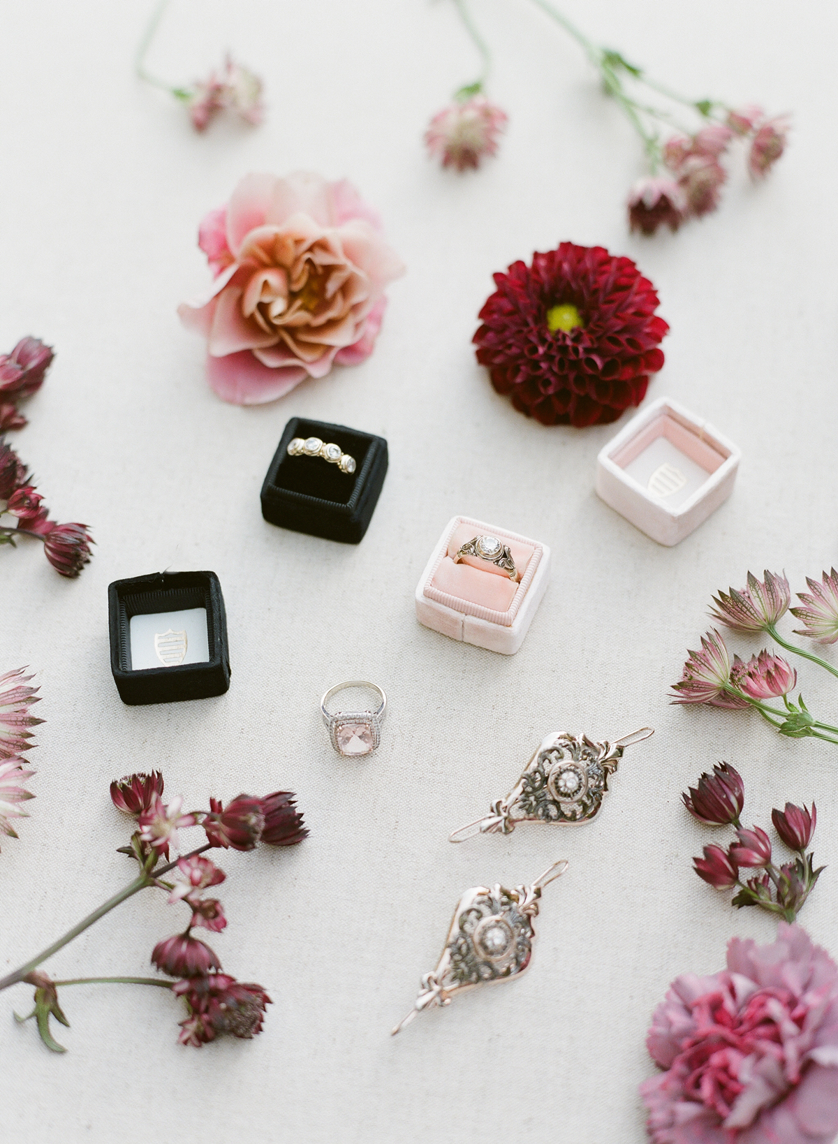 Heirloom earrings and diamond rings surrounded by flowers