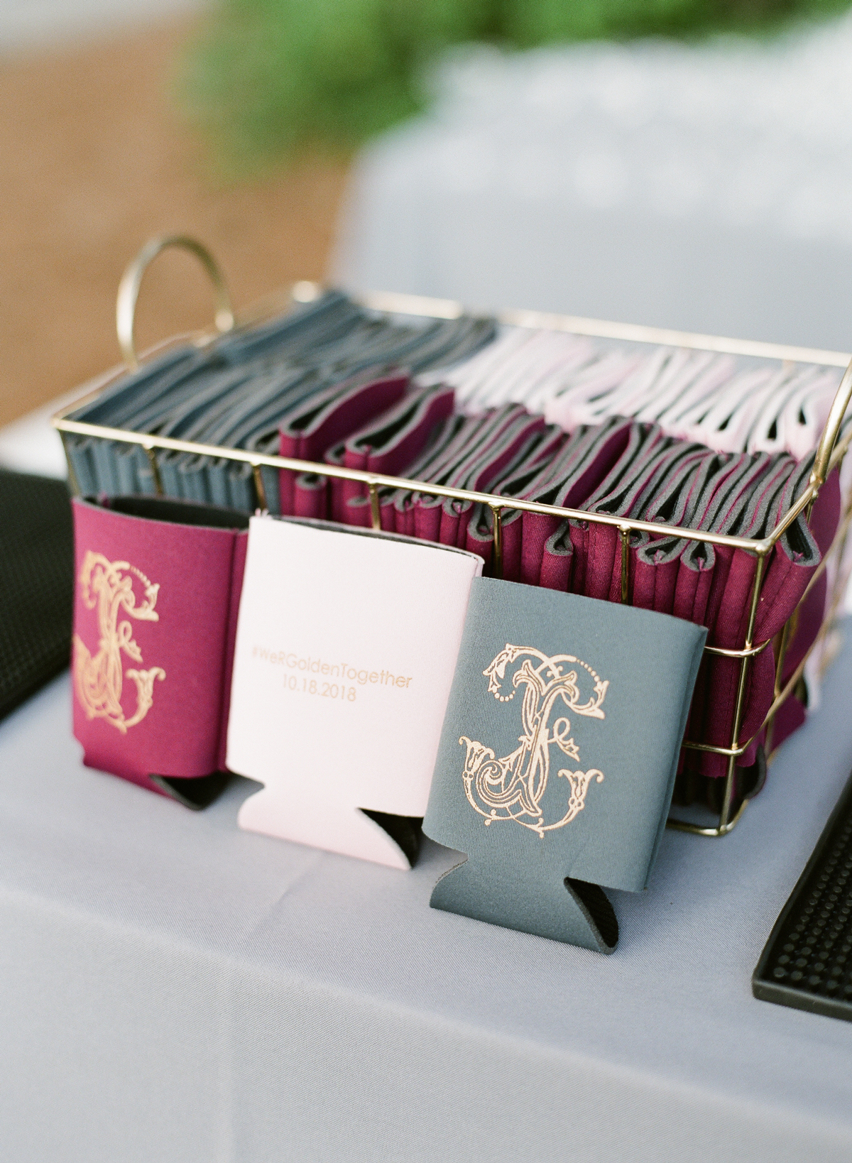 Maroon, white, and forest green koozies with gold customized design