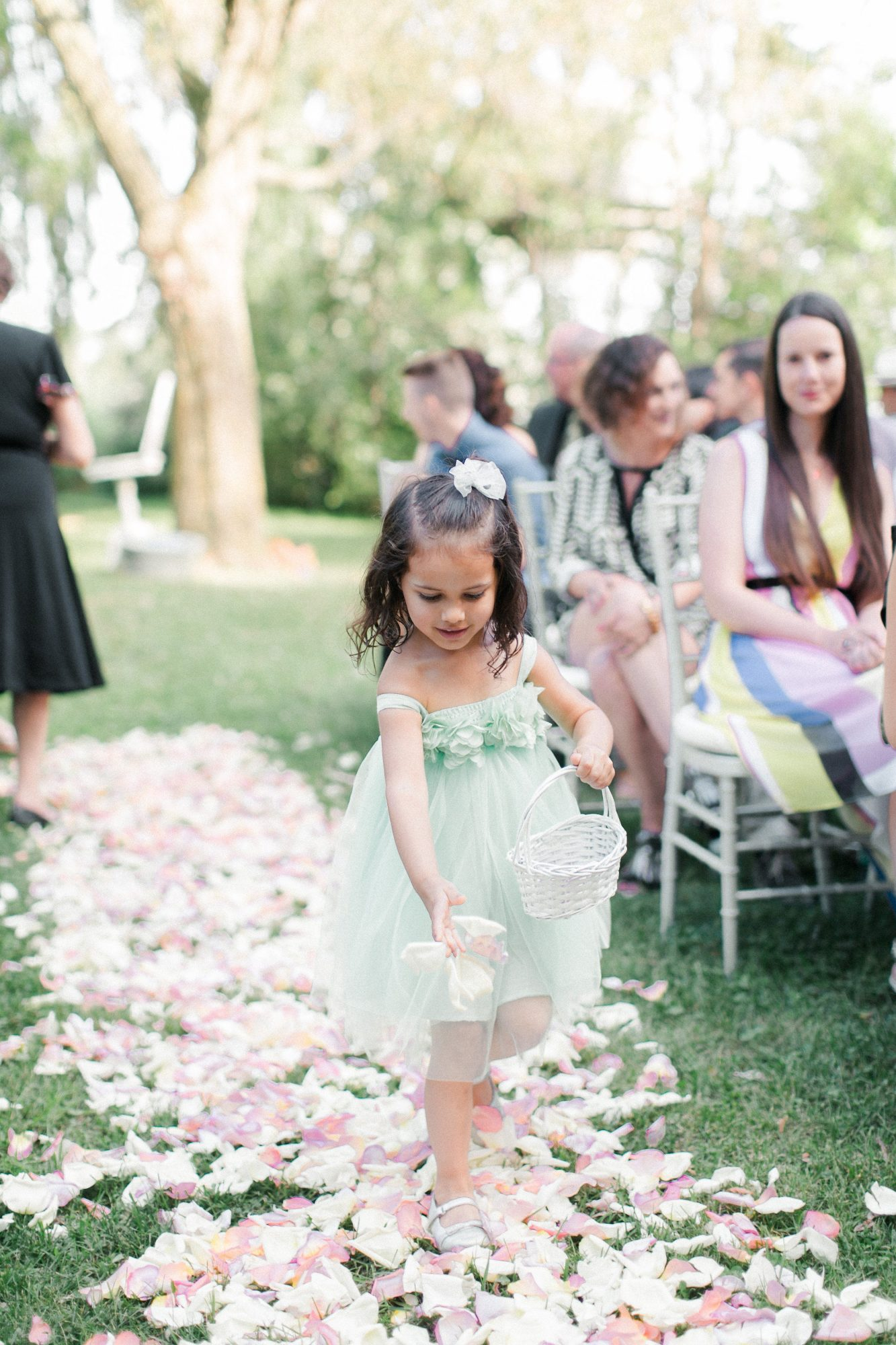 flower girl in green dress dropping petals