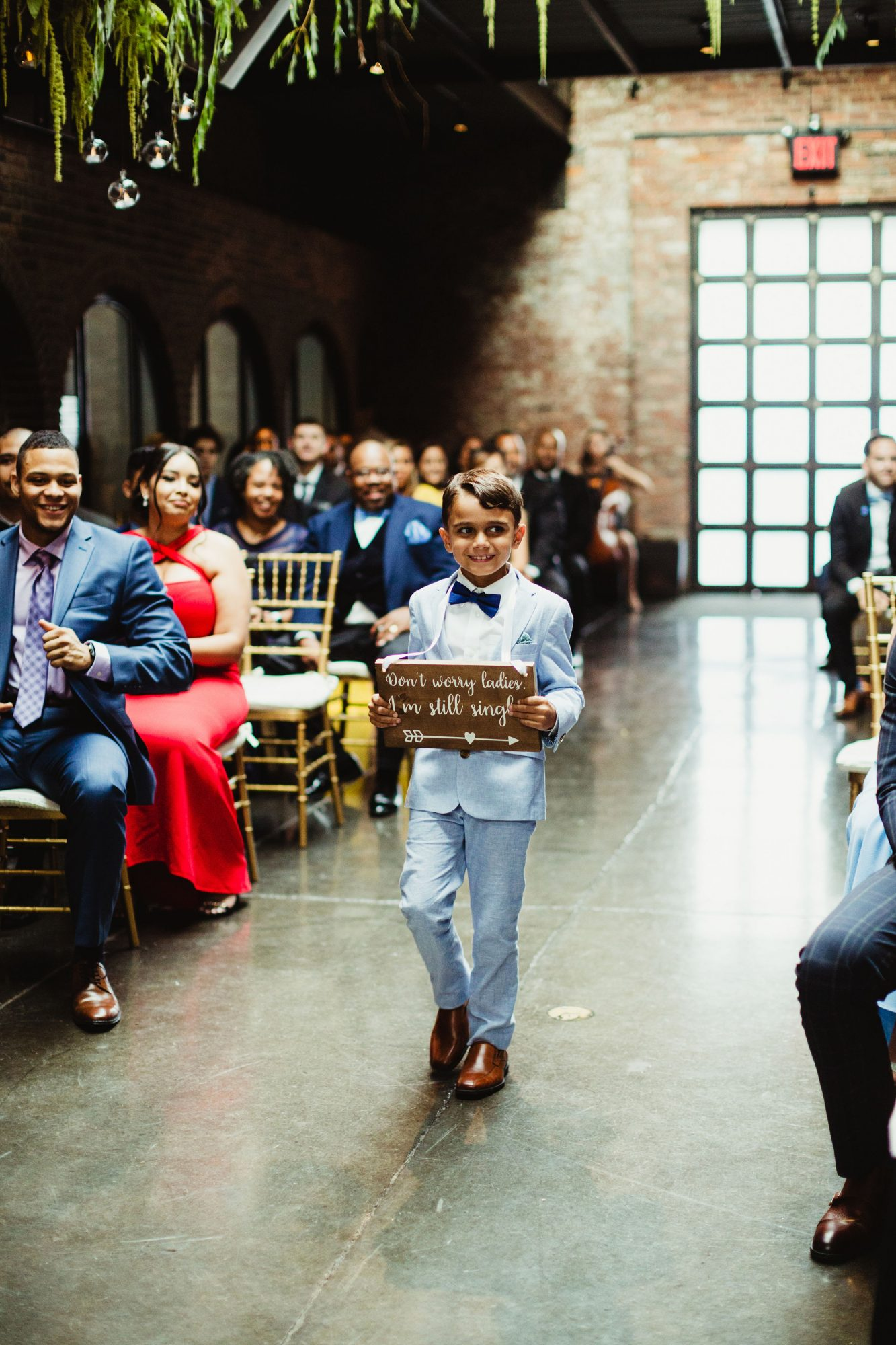 ring bearer walking down the aisle with sign