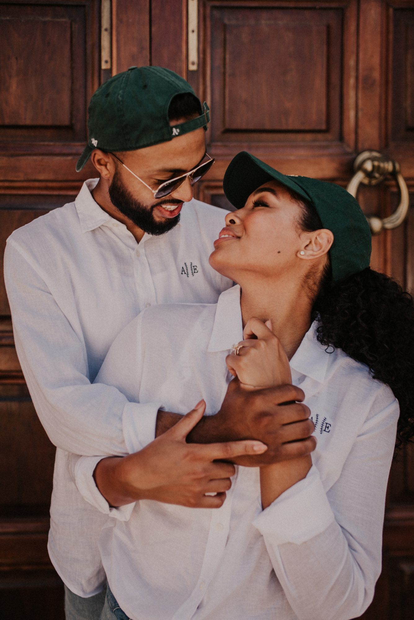 couple stands in matching white dress shirts and green baseball caps