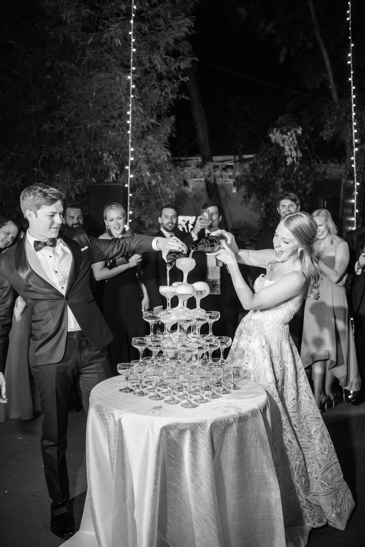 couple pouring champagne over tower of glasses