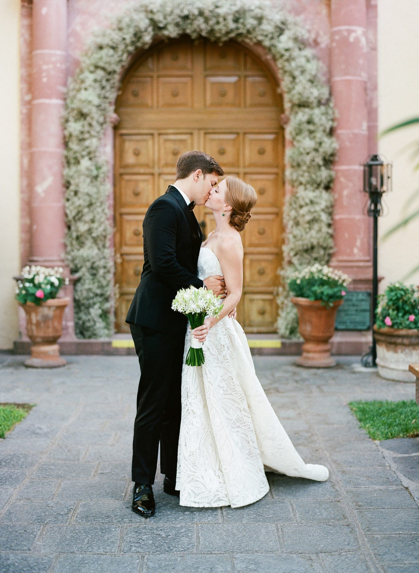 ellery trace mexico wedding bride and groom kissing in front of floral arch