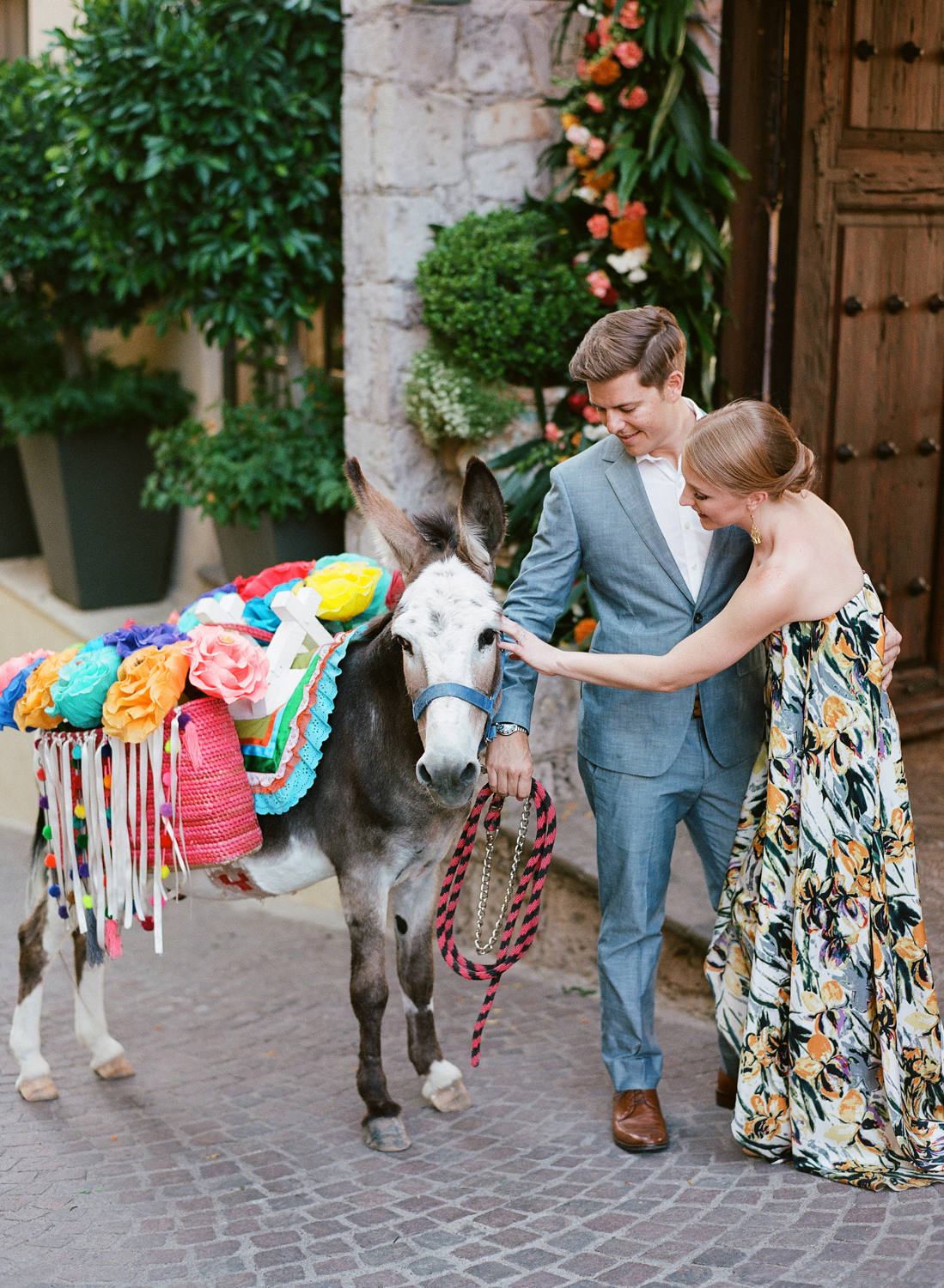 couple petting decorated donkey