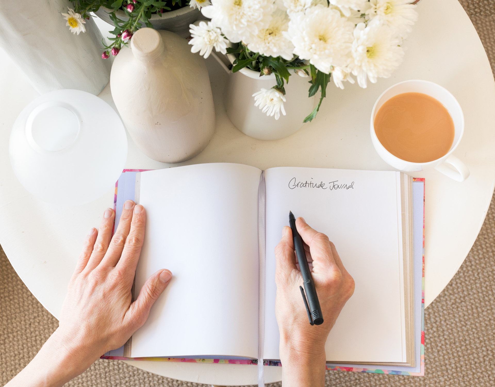 hands writing in journal on table with coffee cup and flowers