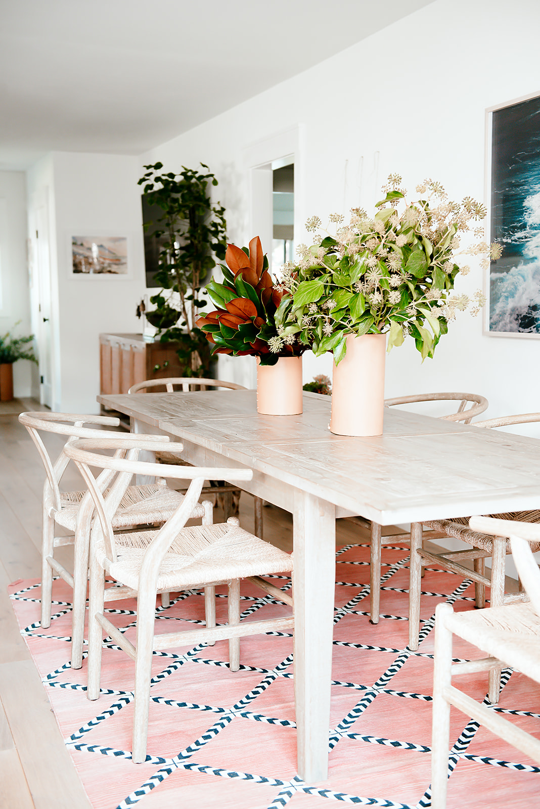 dining table with two vases and coral rug