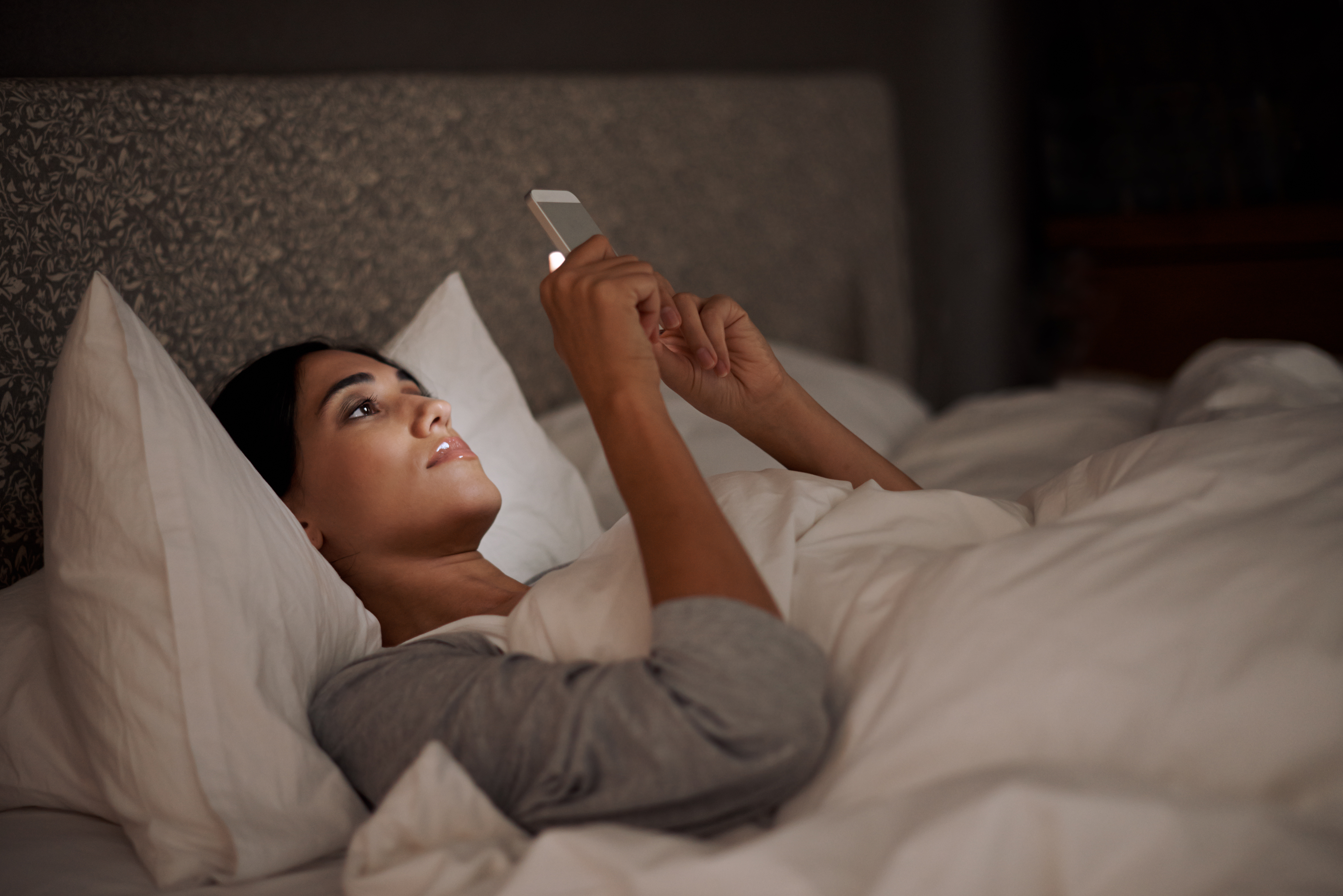 woman in bed looking at cell phone