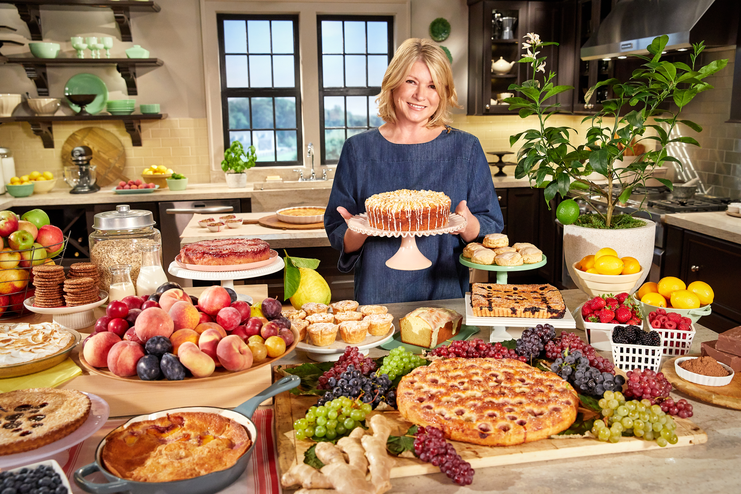 martha in kitchen holding cake surrounded by desserts