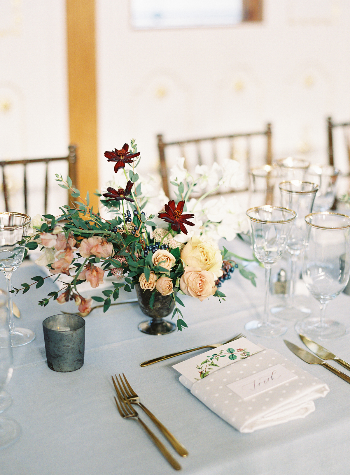 floral centerpieces, blue-grey linen, and gold accented glass tableware