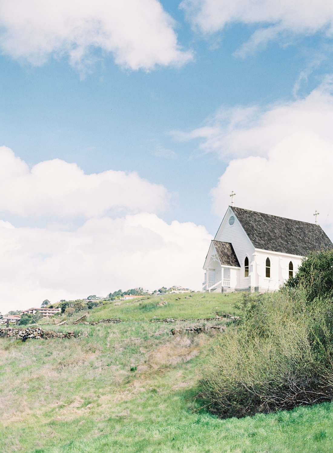 petite white church on top a grassy hill