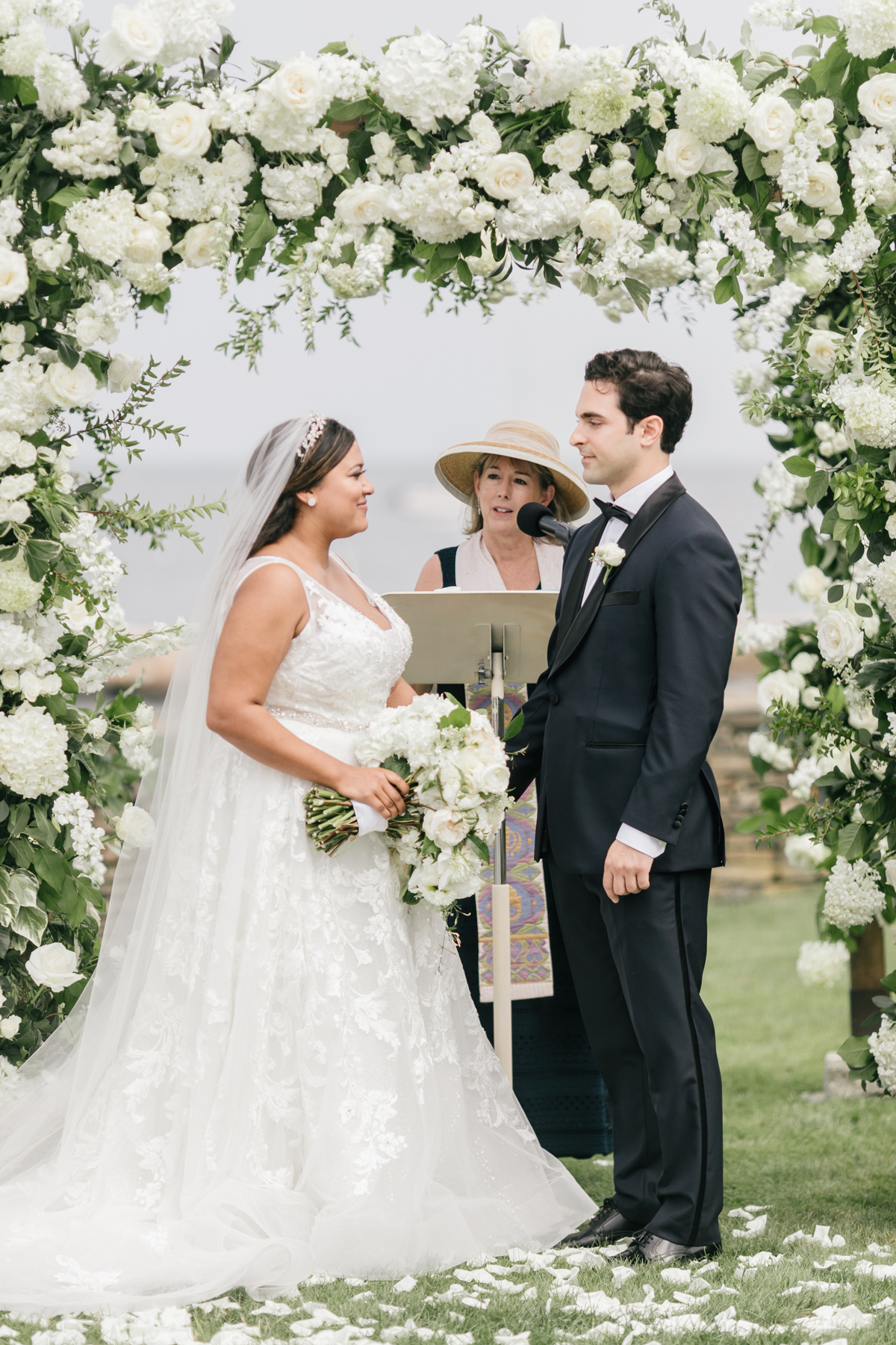 wedding ceremony bride and groom beneath arch of white flowers